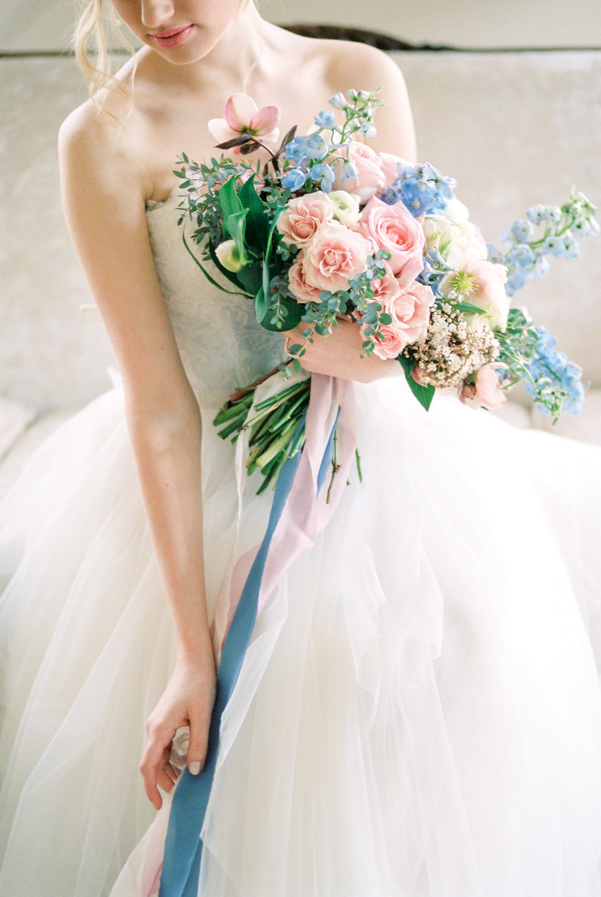 pink and blue ribbons wrapped around pink and blue floral wedding bouquet