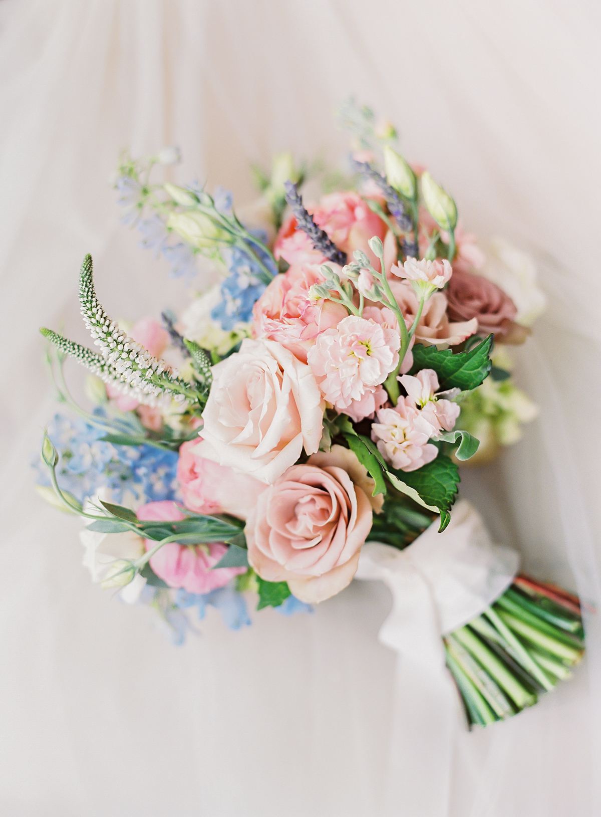 pink and blue even stem cut bouquet with white ribbon