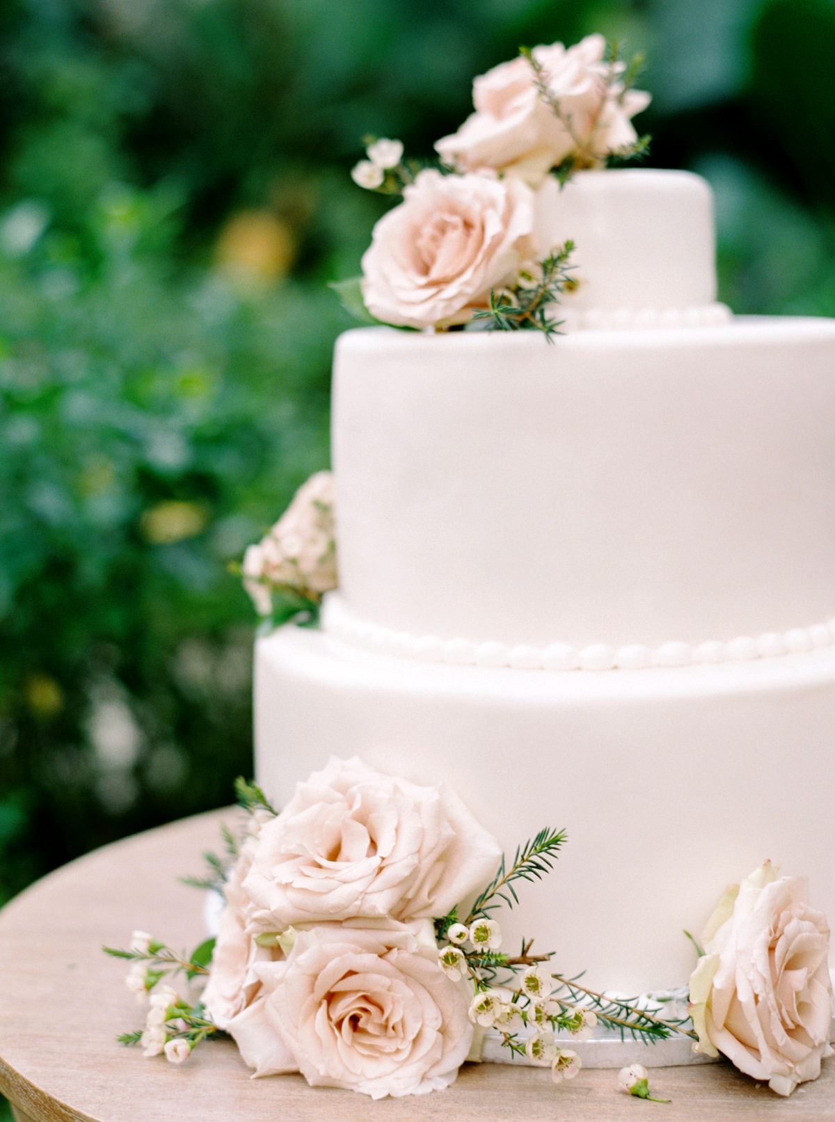 three-tier white wedding cake decorated flowers