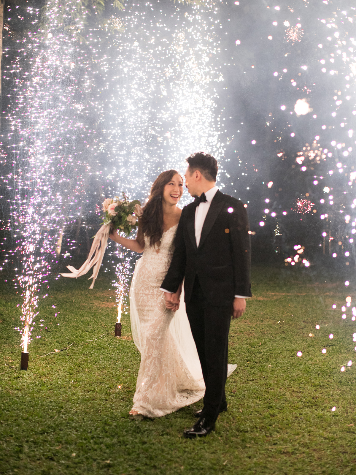 bride and groom smiling under sparklers