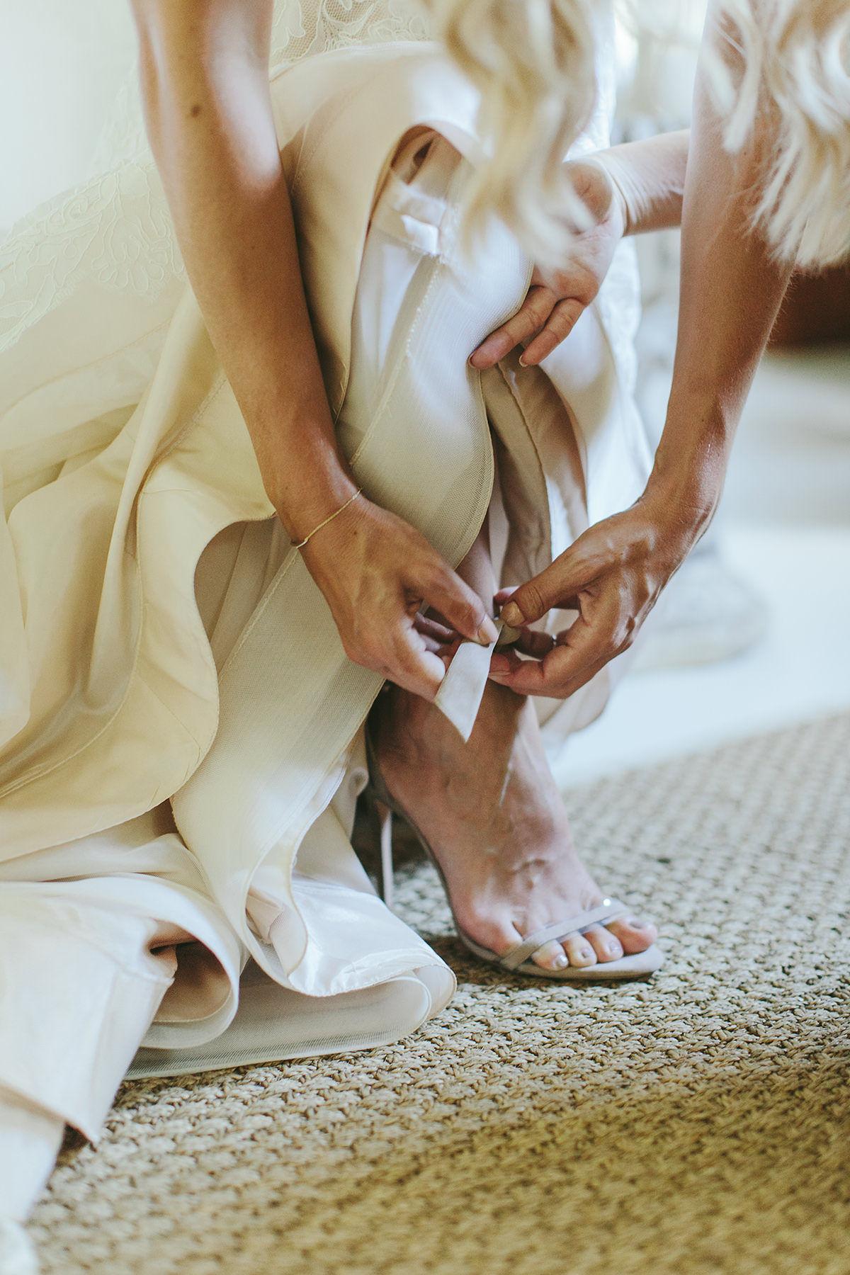 sarah daniel wedding bride putting on shoes
