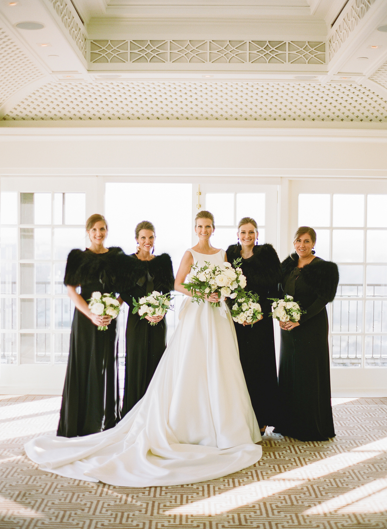 bride with bridesmaids wearing various styled long black dresses with black fur shawls