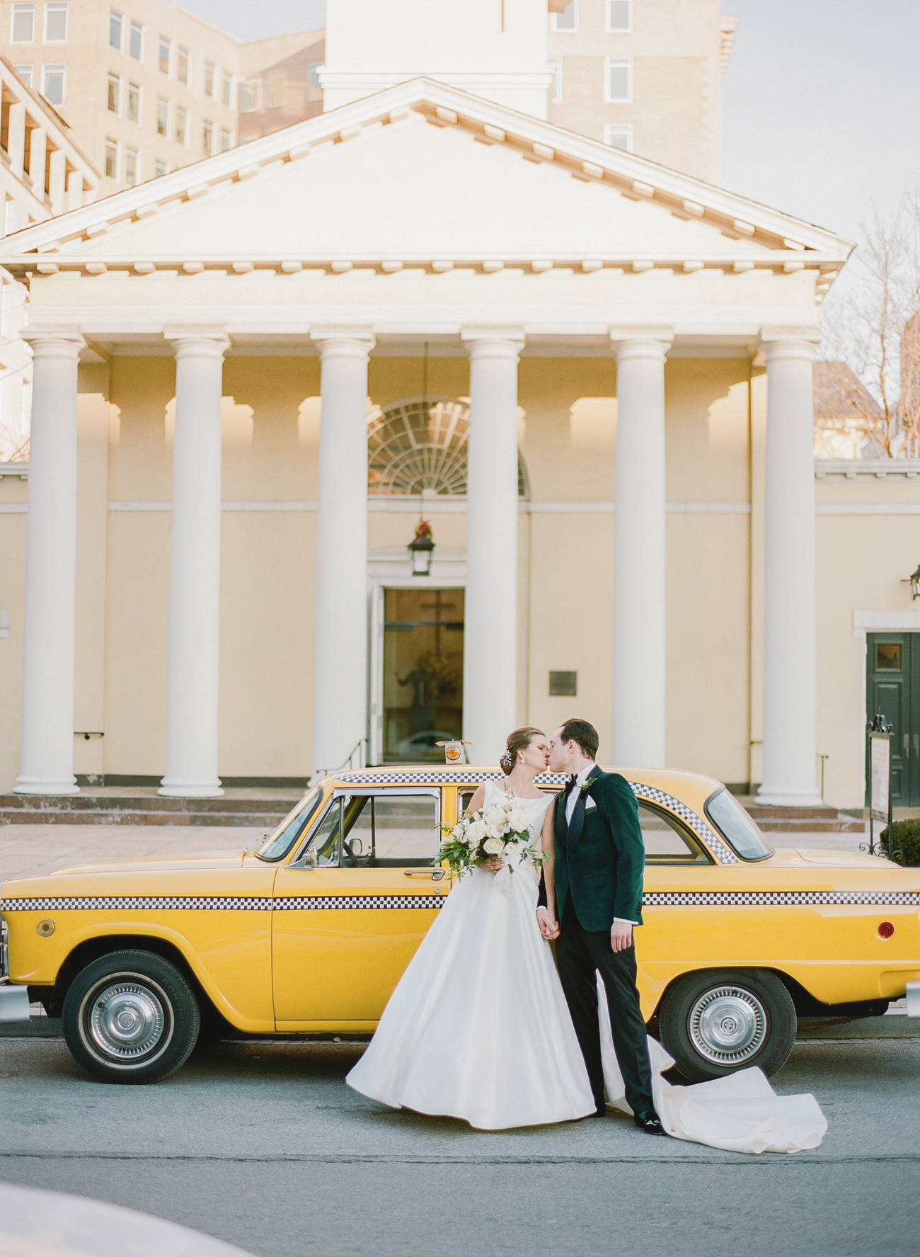 bride and groom standing next to taxi cab outside