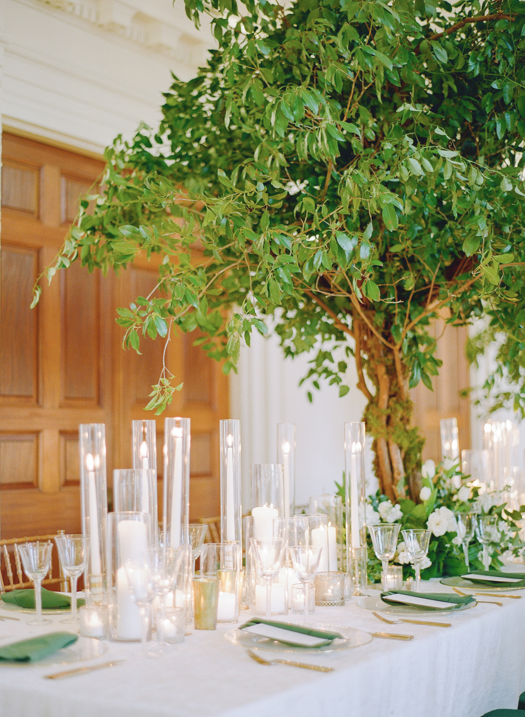 faux tree table decor with white and green reception theme