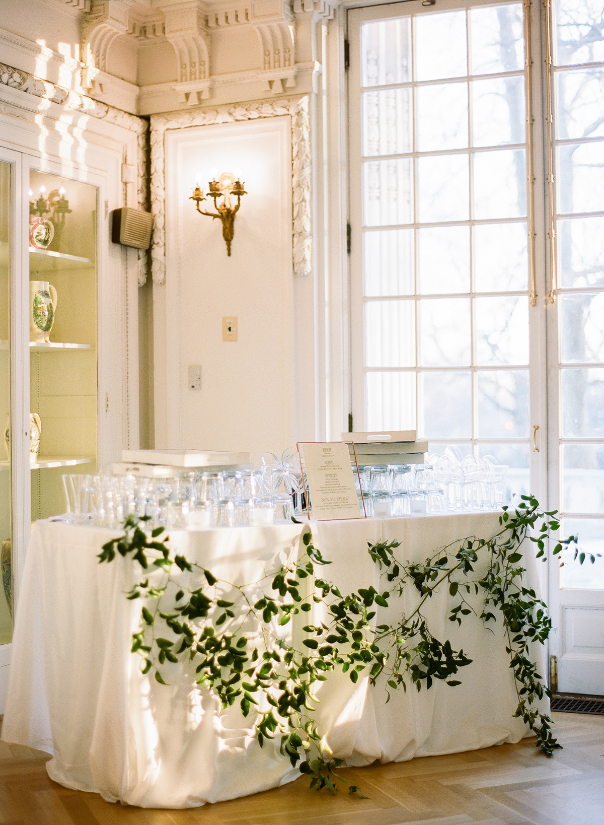 white linen covered cocktail bar table with greenery decor