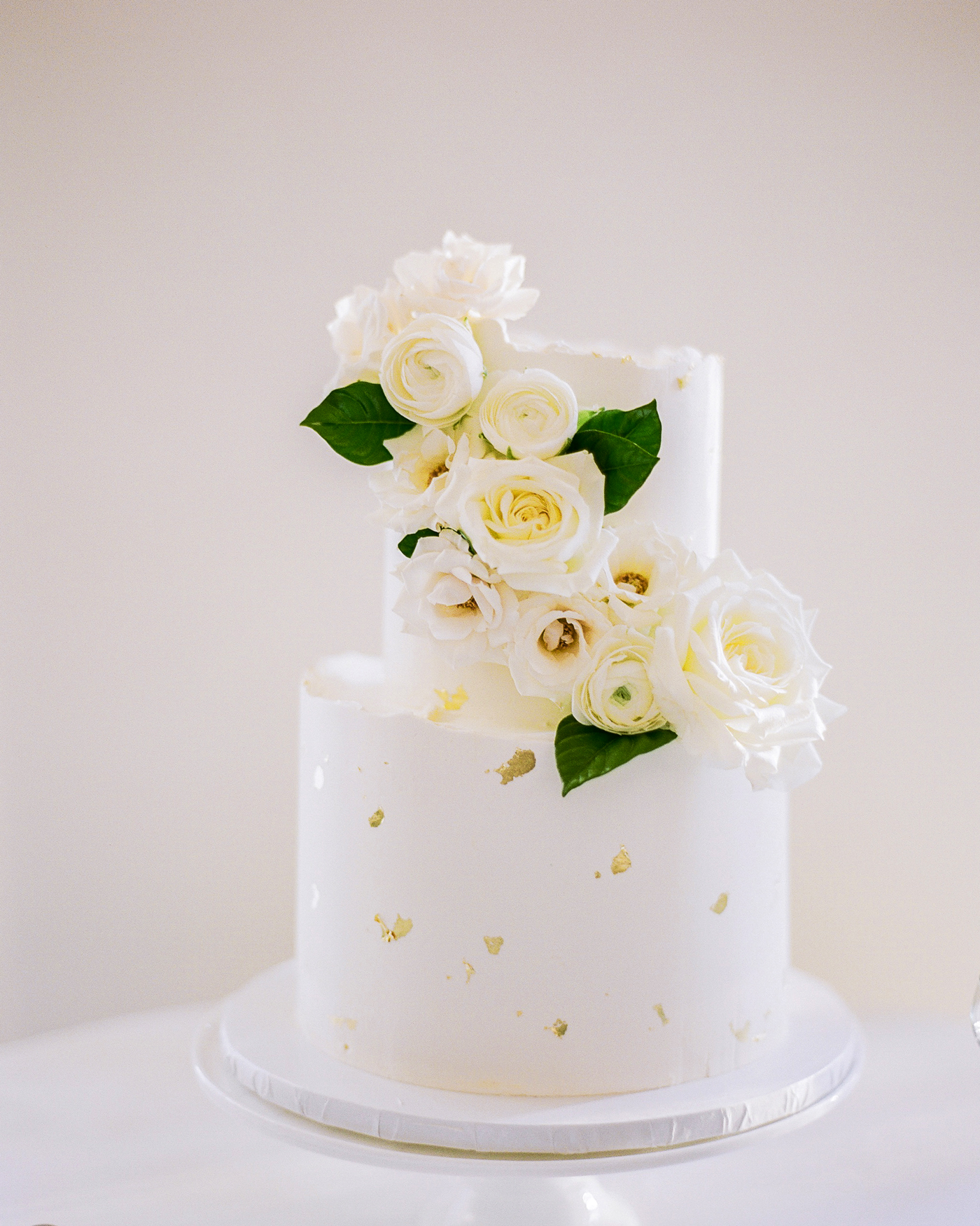 two-tier white frosted gold leaf detailed wedding cake with floral topper