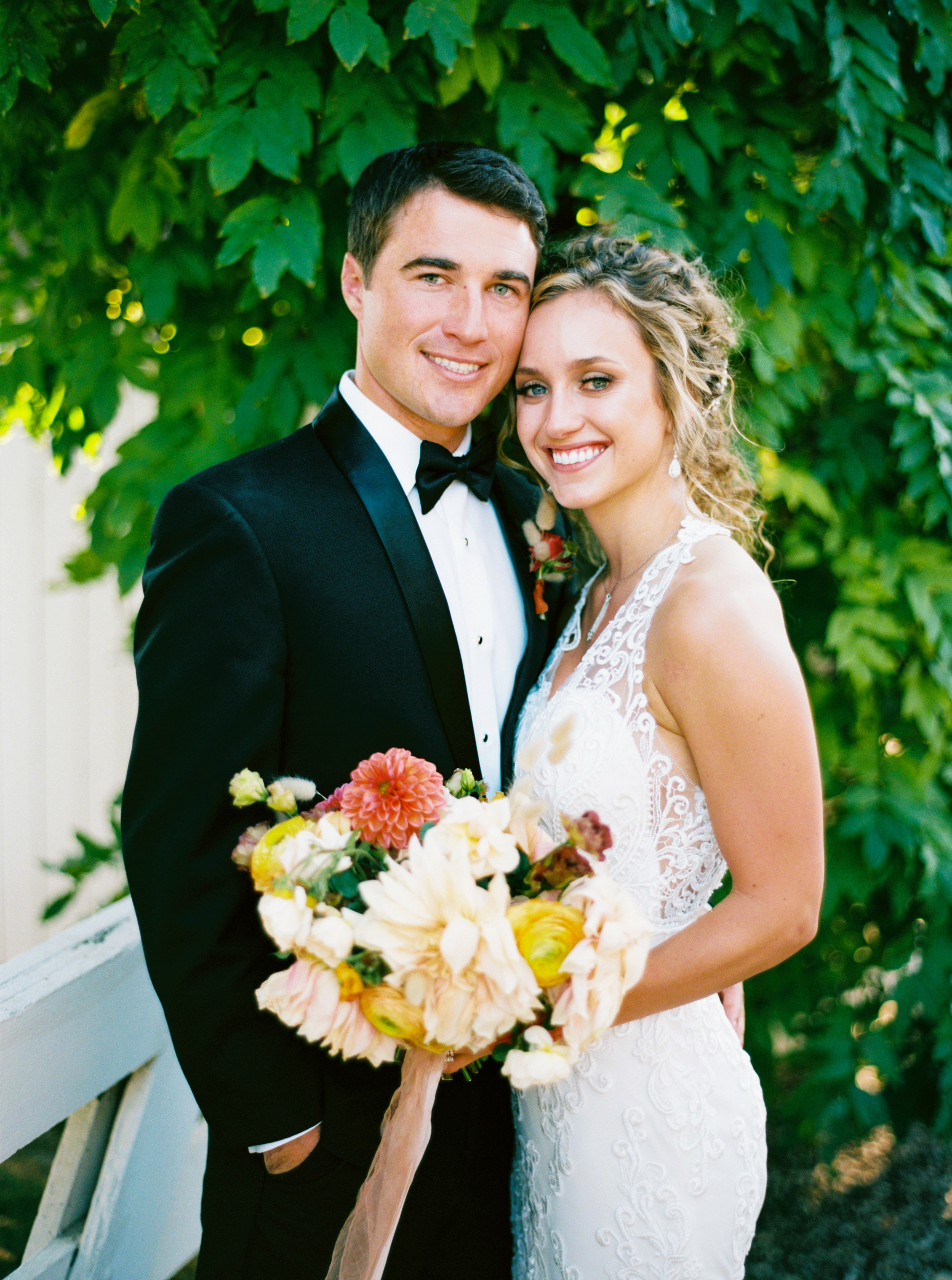 bride and groom pose in wedding attire outdoors