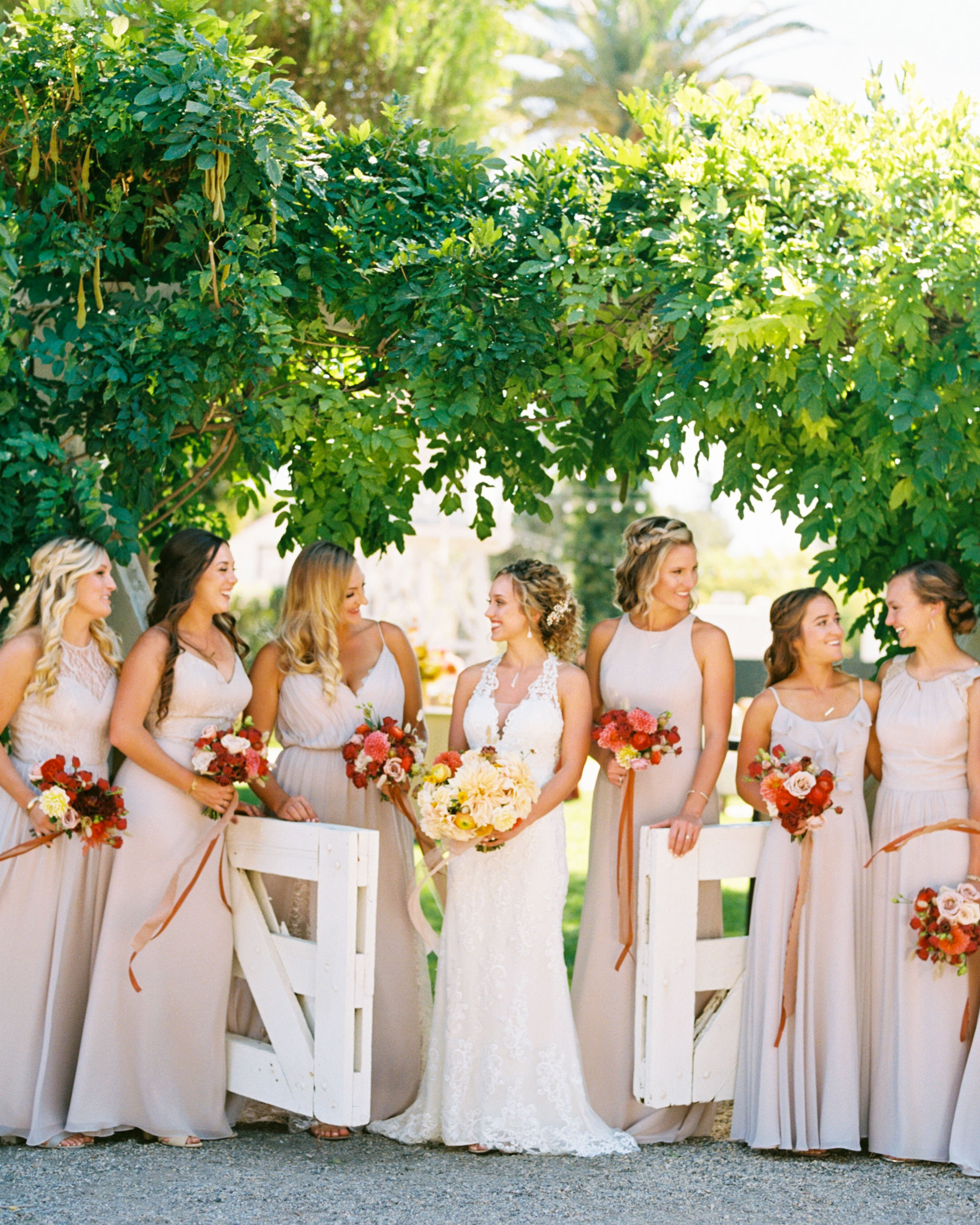 bride and bridesmaids posing under greenery