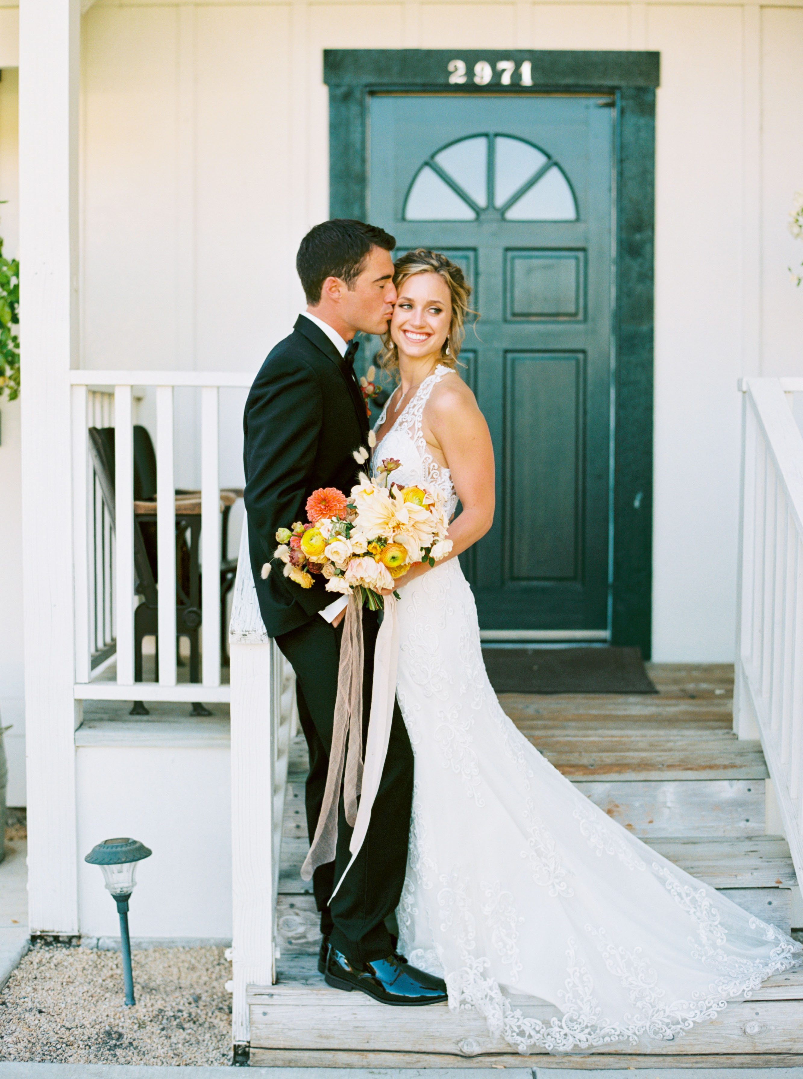 groom kisses bride on front porch steps