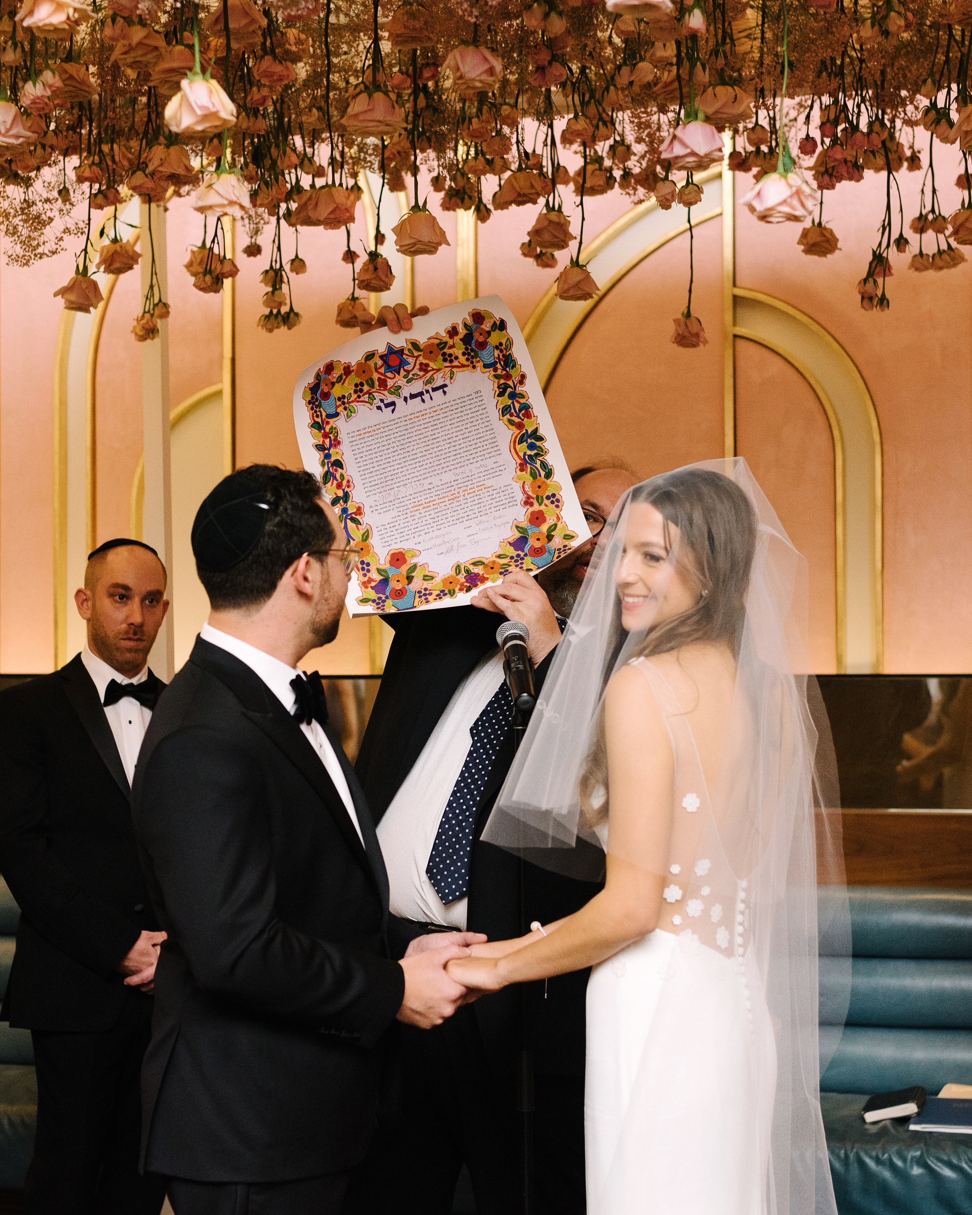 krista will wedding ceremony flowers over bride and groom