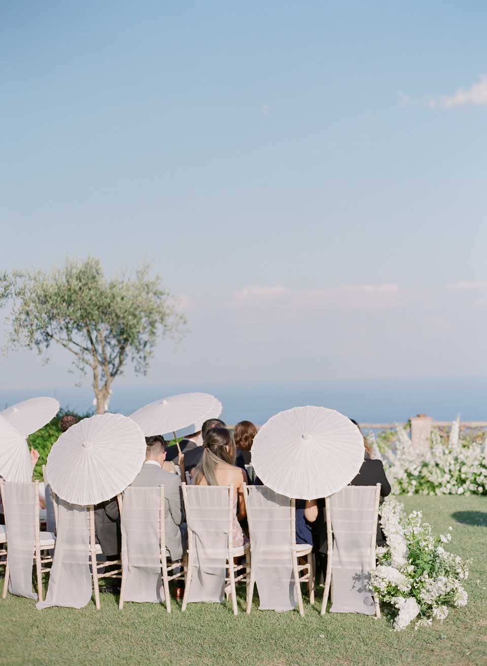 adrienne cameron wedding ceremony guests holding parasols