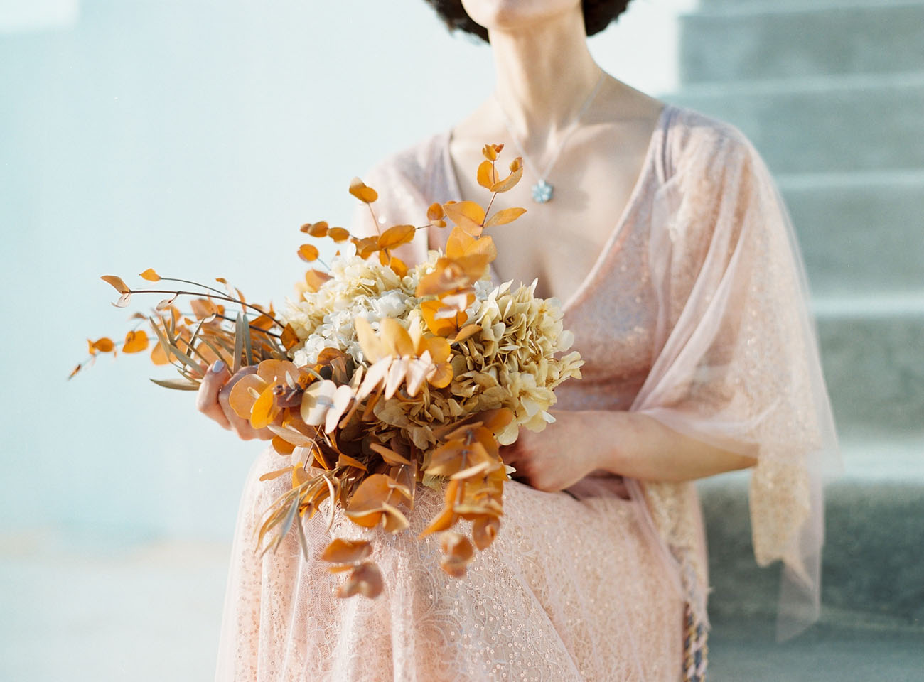 dried wedding bouquet of palm leaves, hydrangeas, and orange leaves