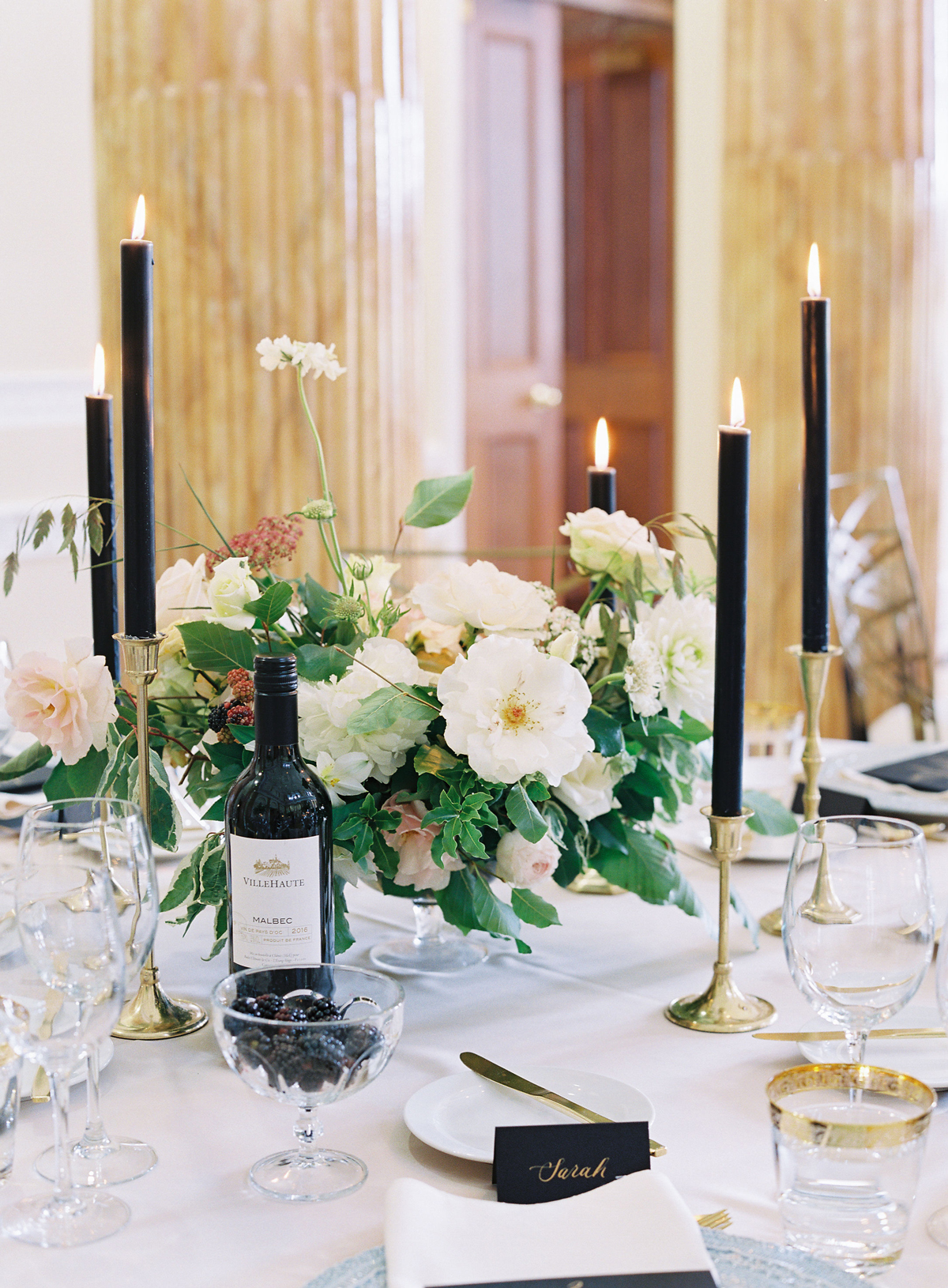 short floral centerpieces and tall black candles reception table decor