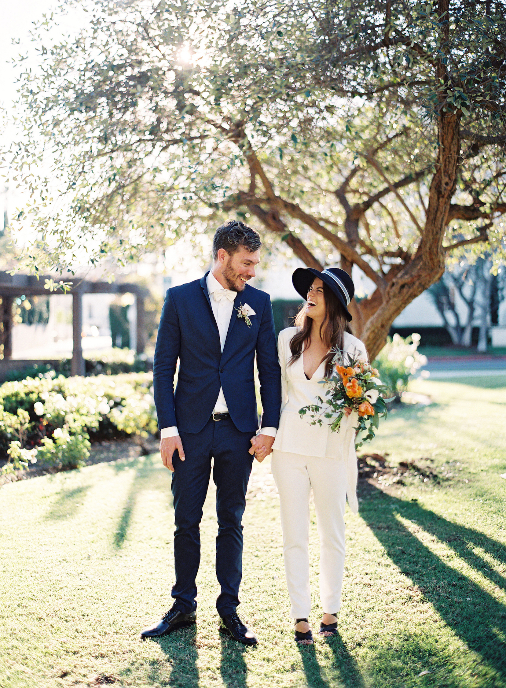 Bride in a Pantsuit Holding the Groom's Hand