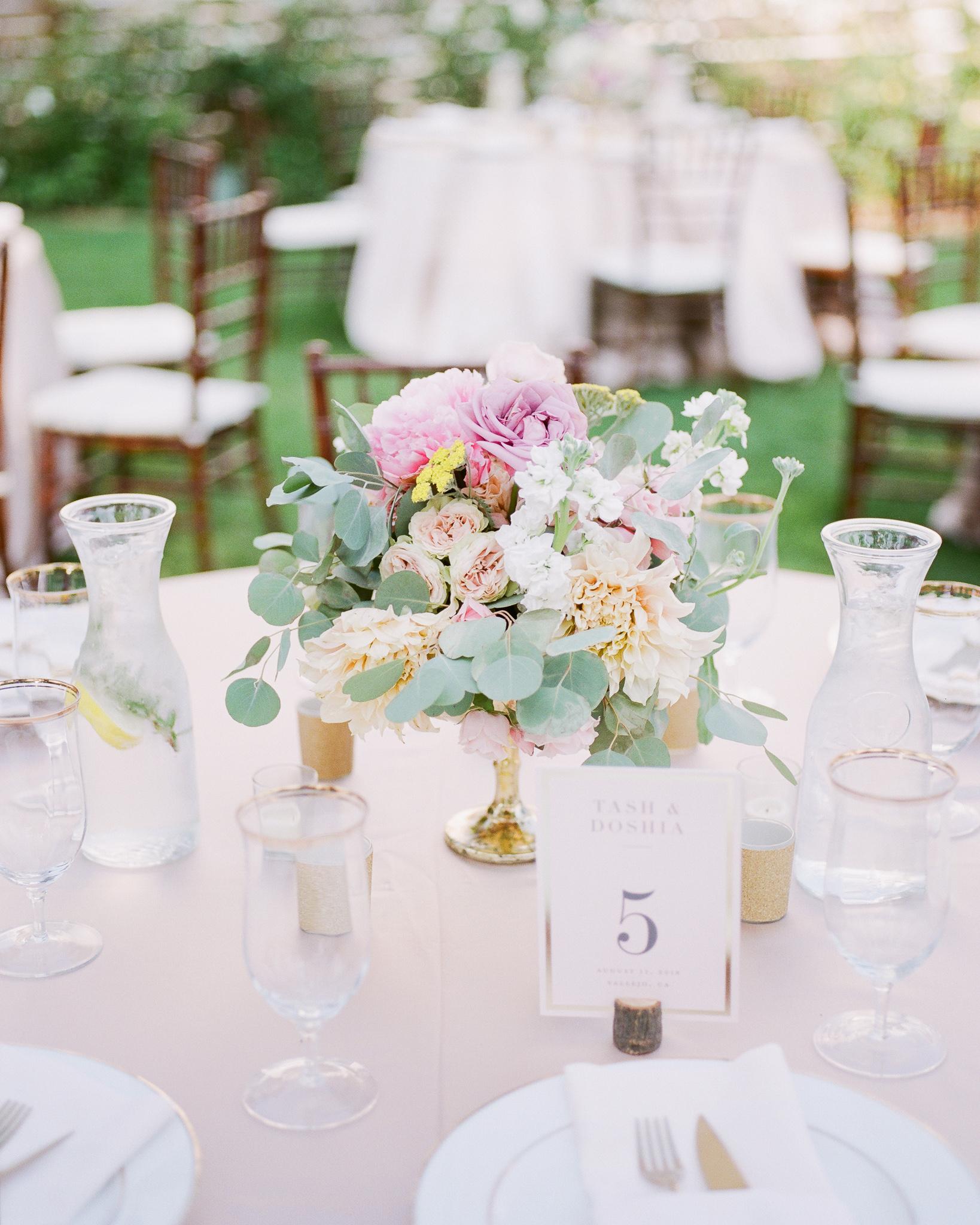 floral arrangement centerpiece in gold vessel plus table number