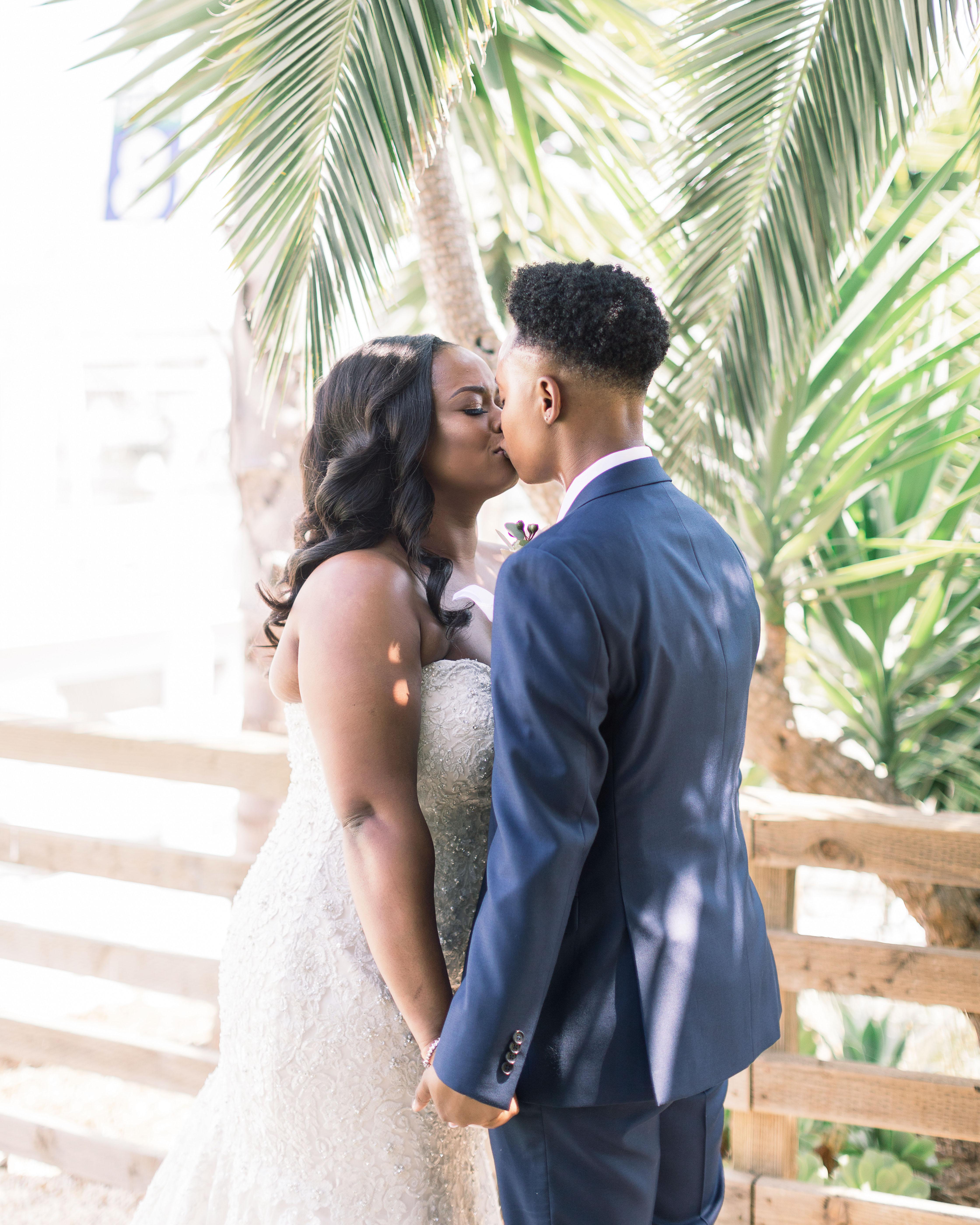 outdoor wedding kiss under tropical tree