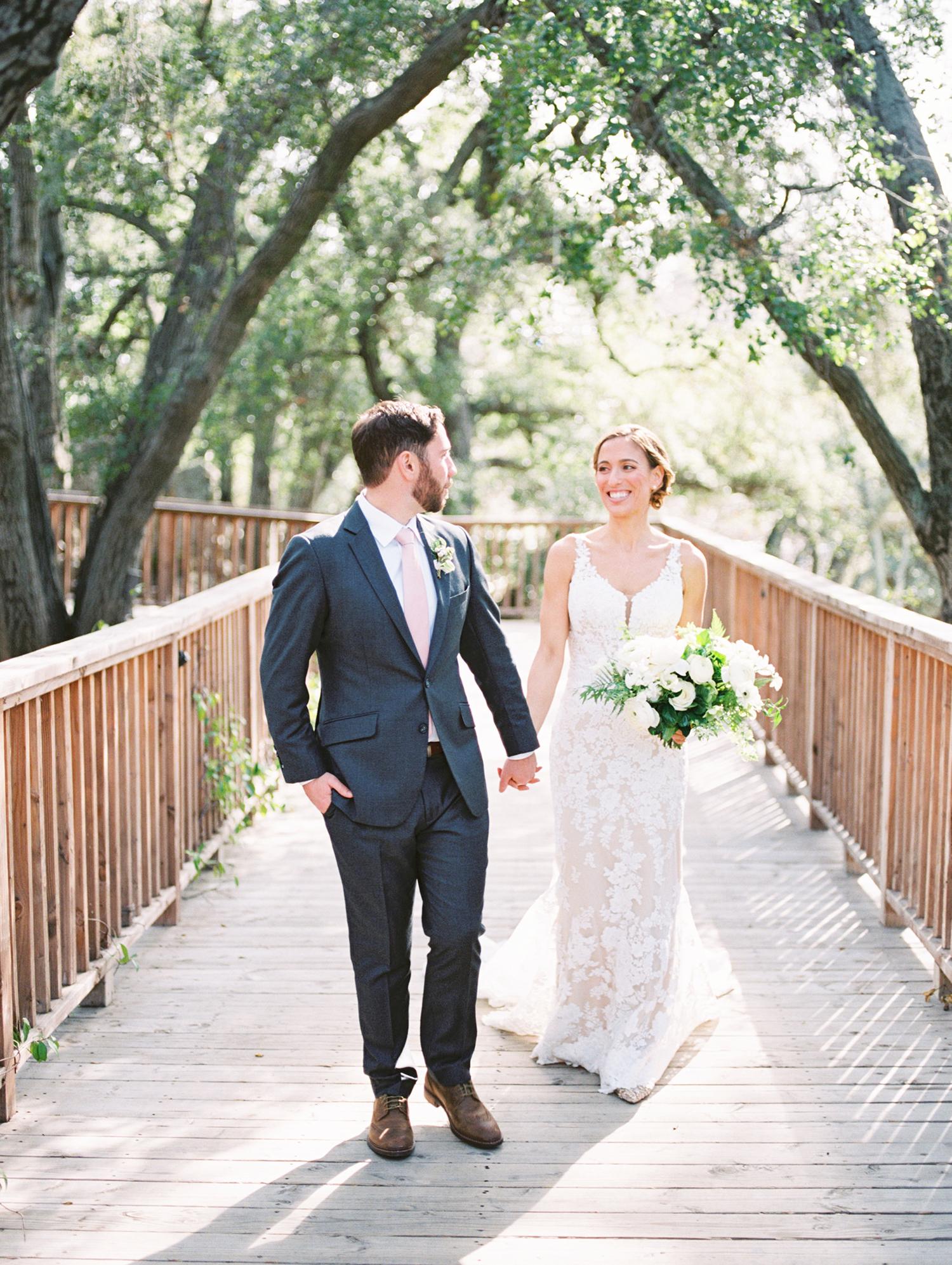 lauren aaron wedding couple holding hands on bridge