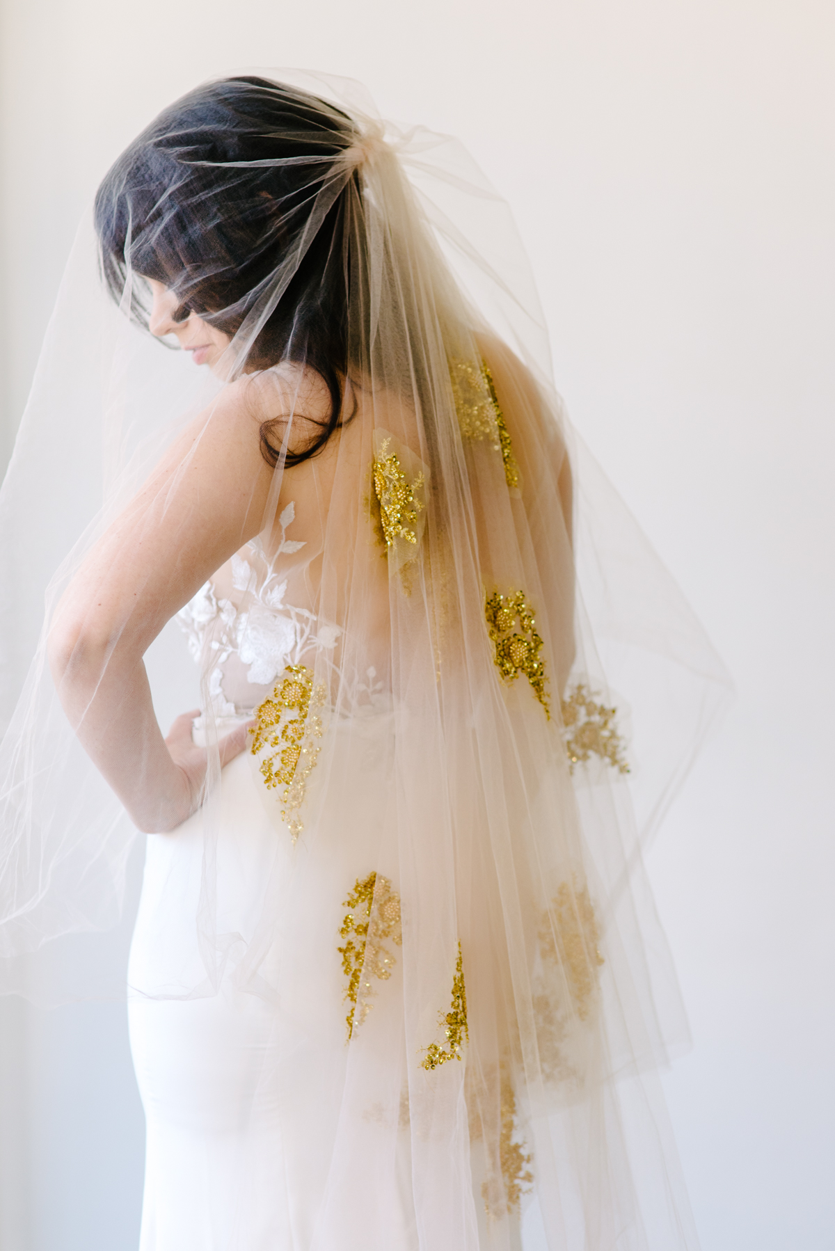 bride wearing veil with gold appliqués