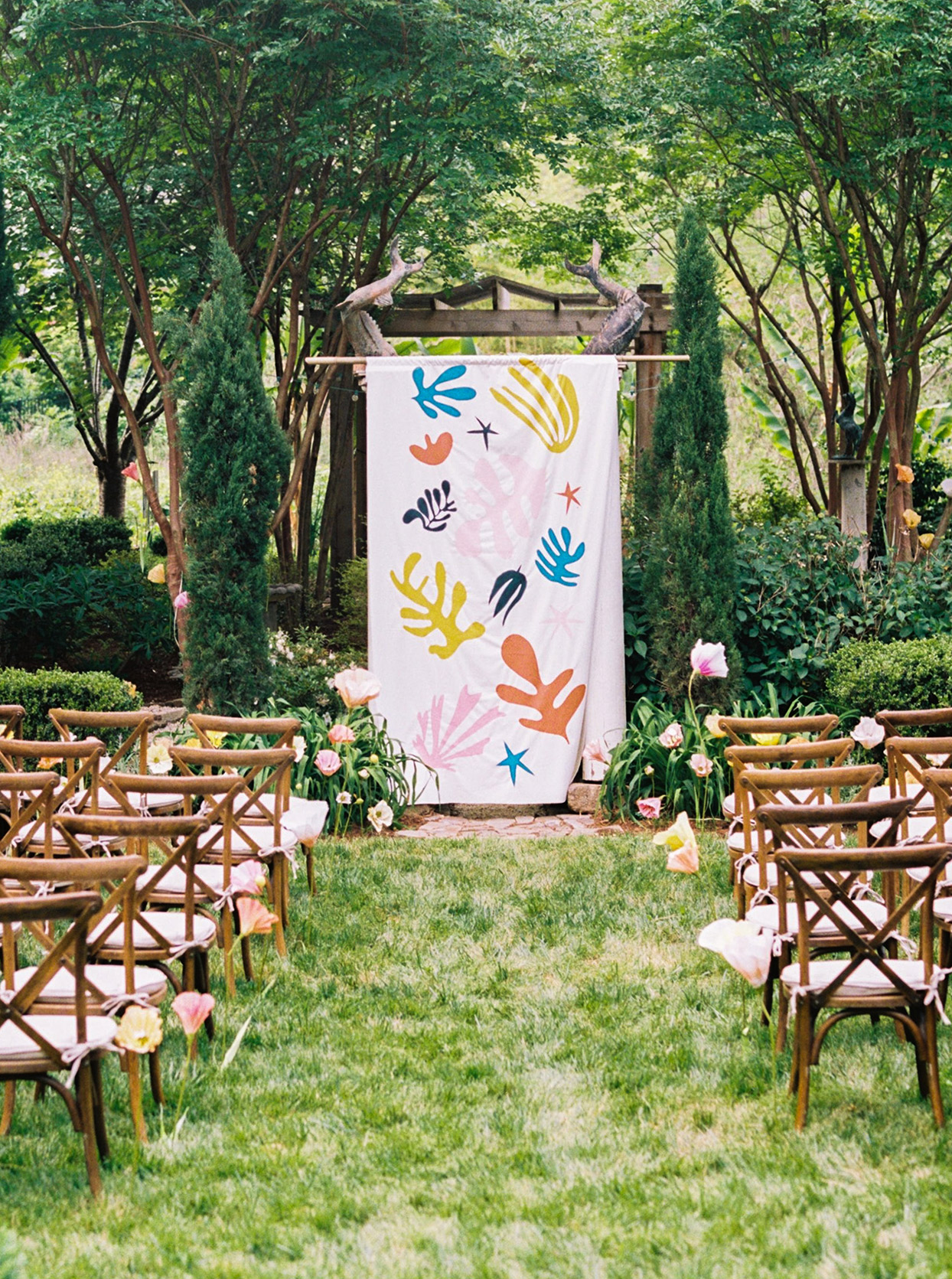 ashley scott wedding ceremony colorful backdrop wooden chairs