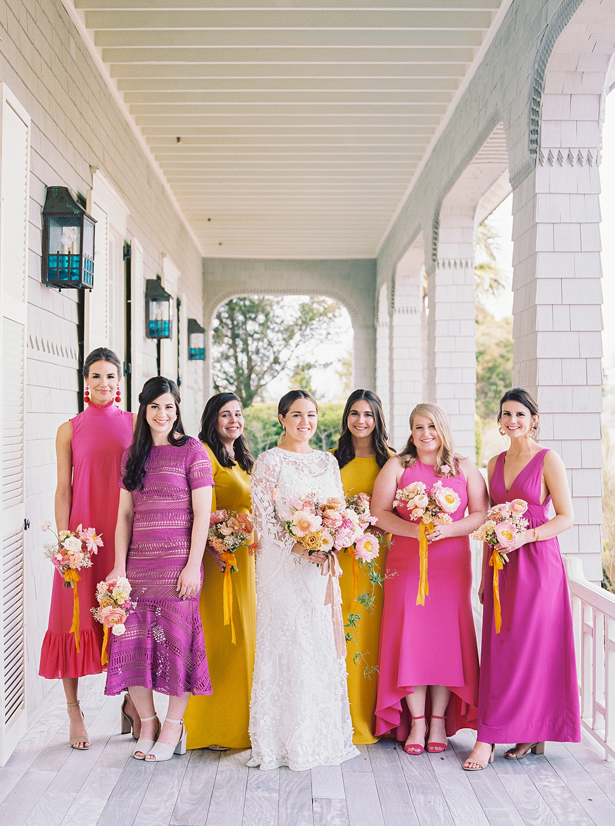 lauren dan wedding bridesmaids in colorful yellow and pink dresses