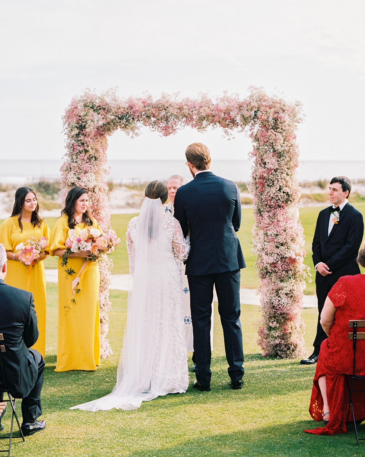 lauren dan wedding ceremony officiant and couple by floral arch