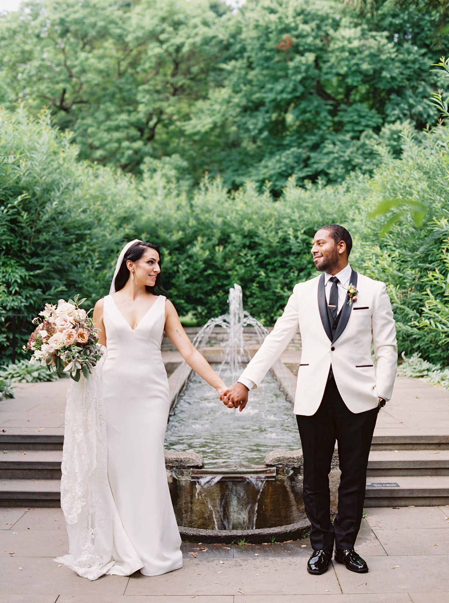 noel mike wedding couple holding hands by fountain