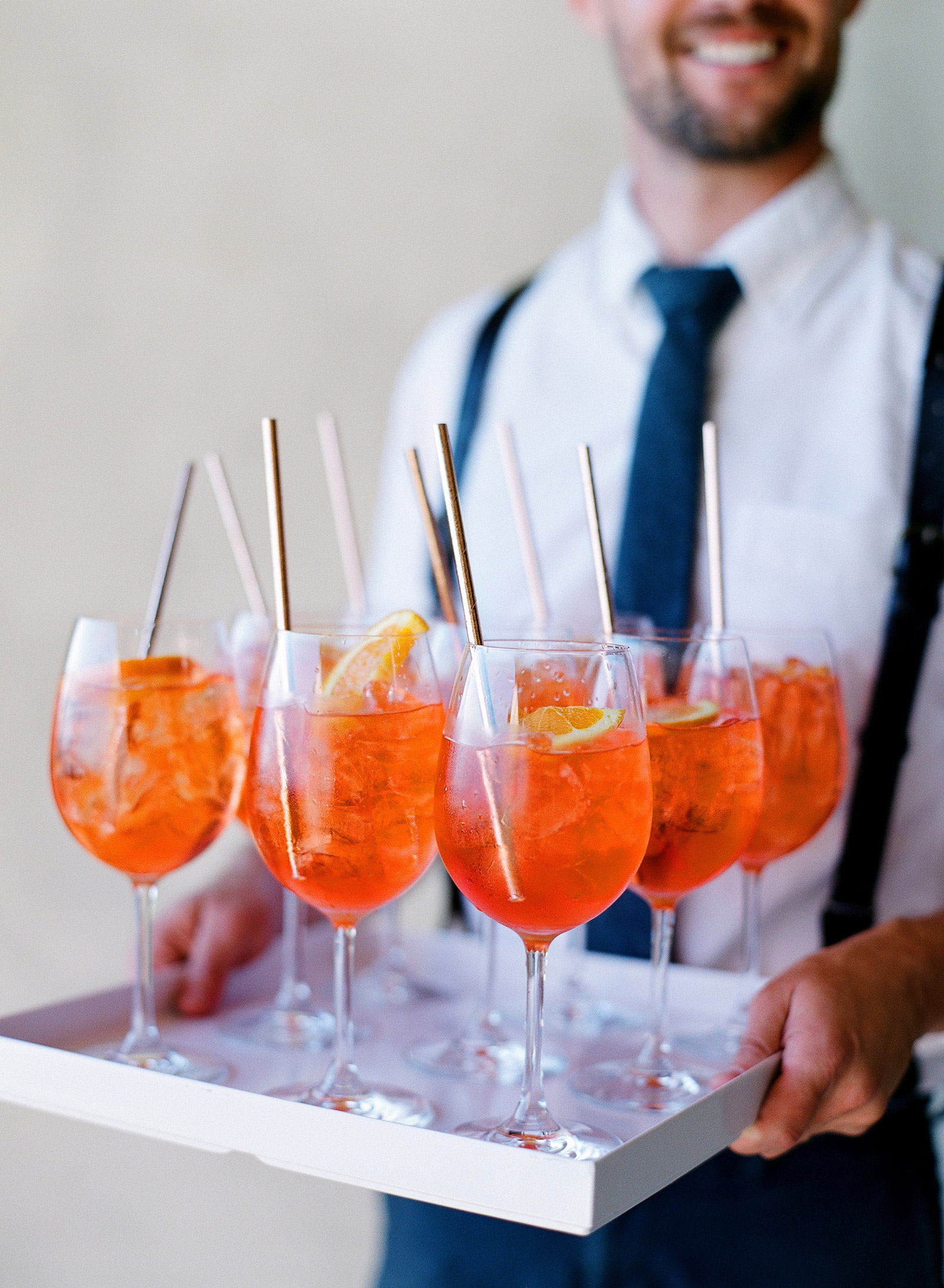 man carrying tray of aperol-spritz
