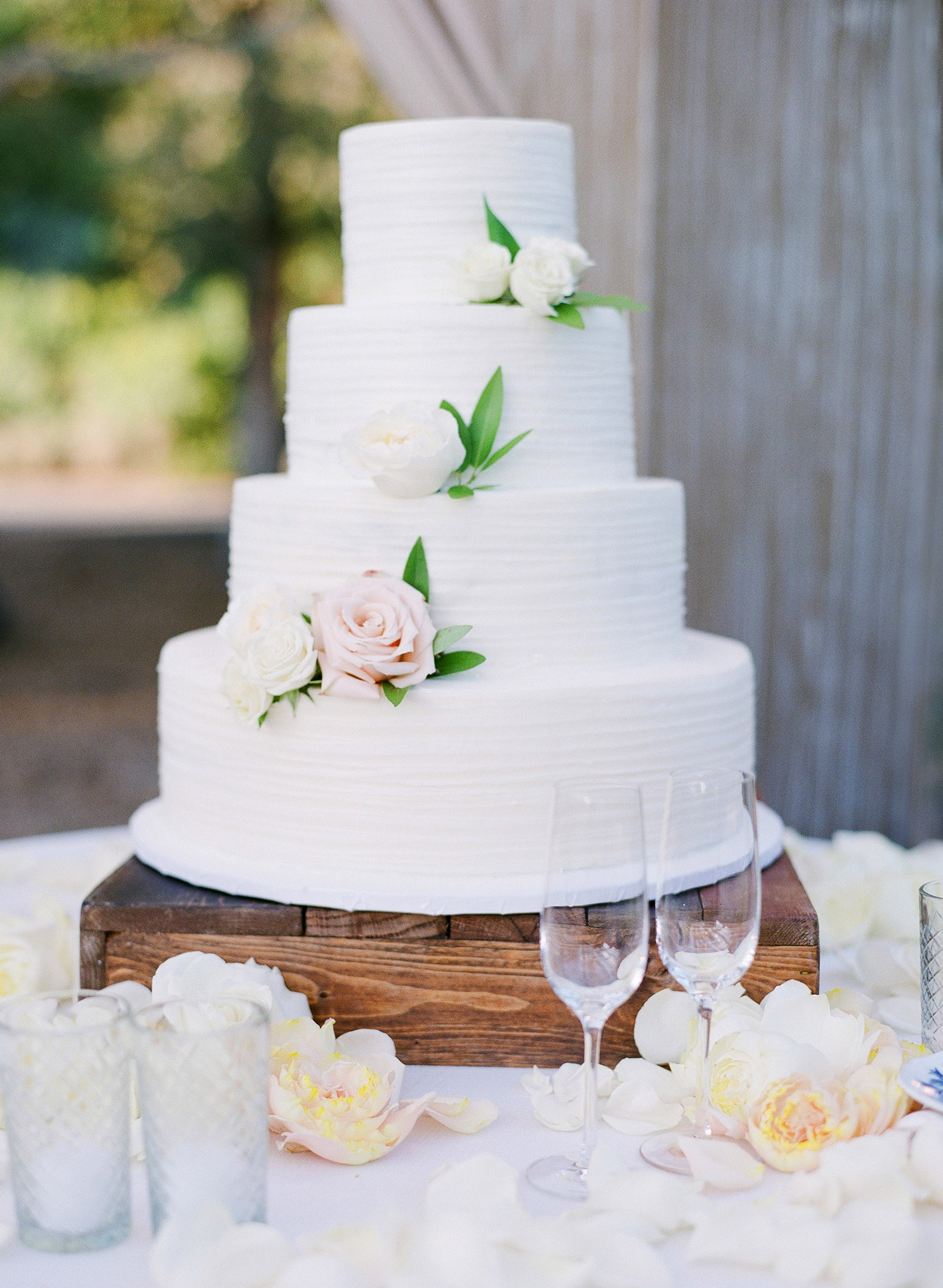 4-tier white wedding cake decorated with a few roses