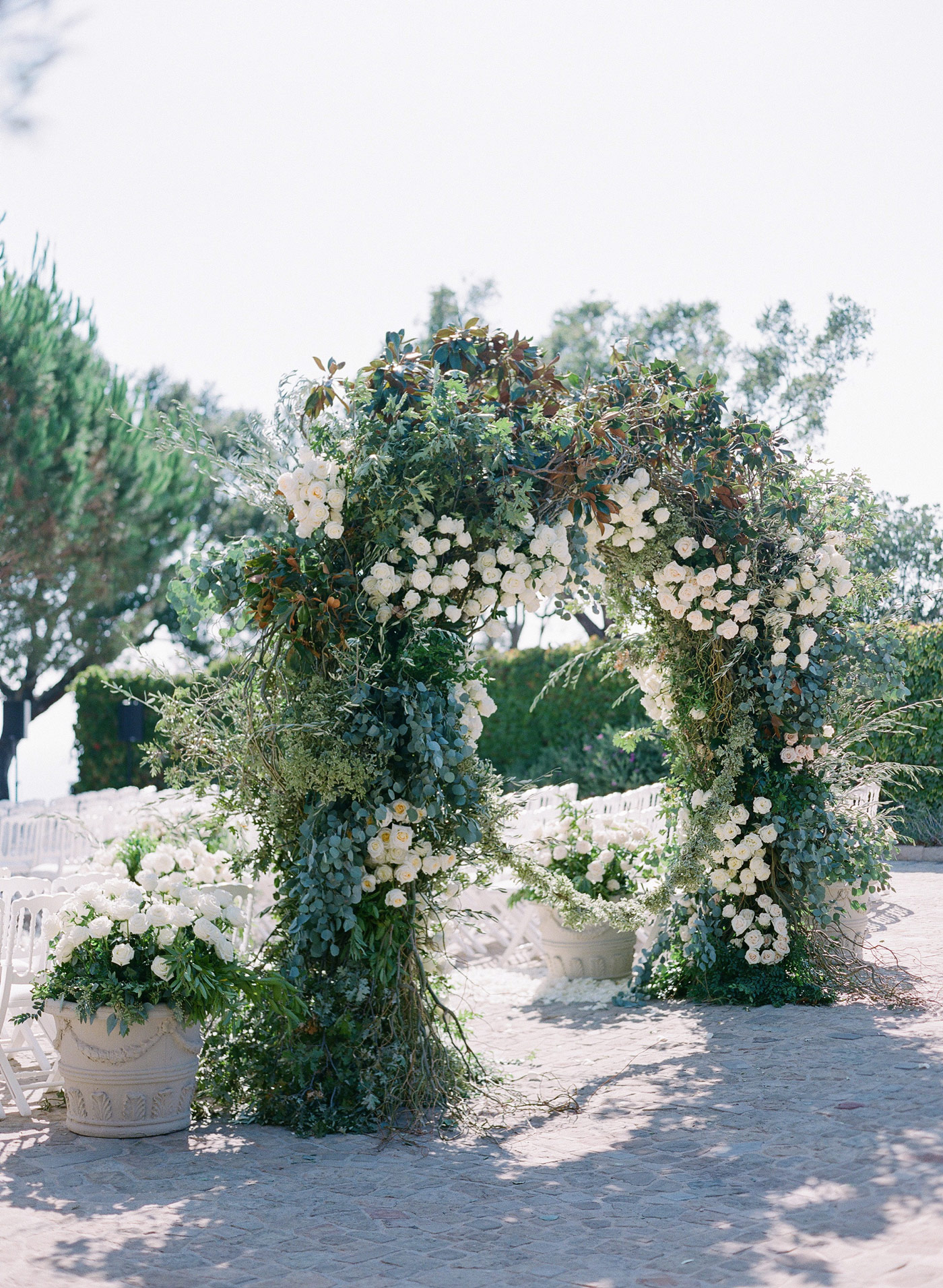 wedding ceremony arch decorated in greenery and white roses