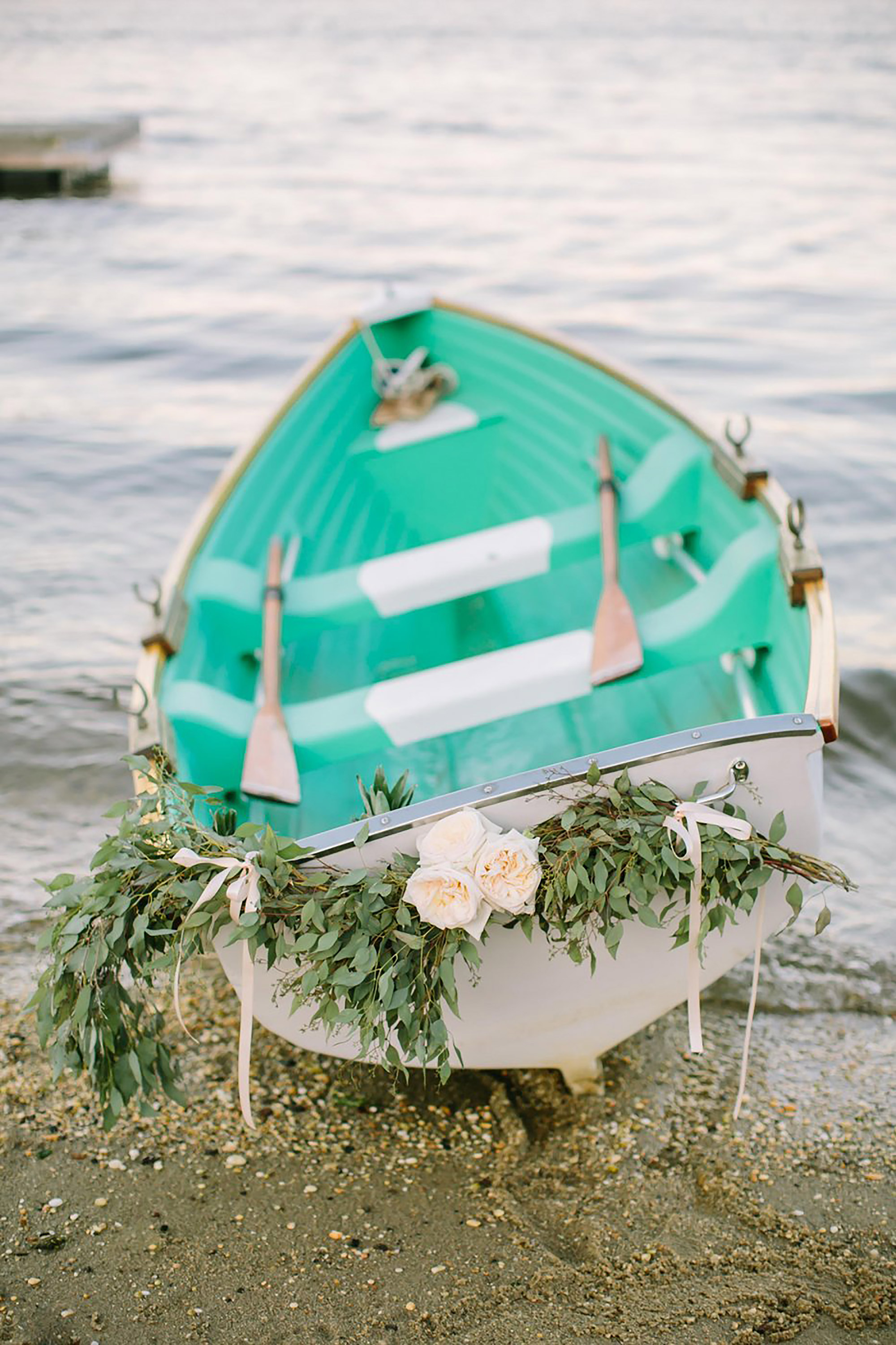 white canoe decorated in greenery white roses ribbon