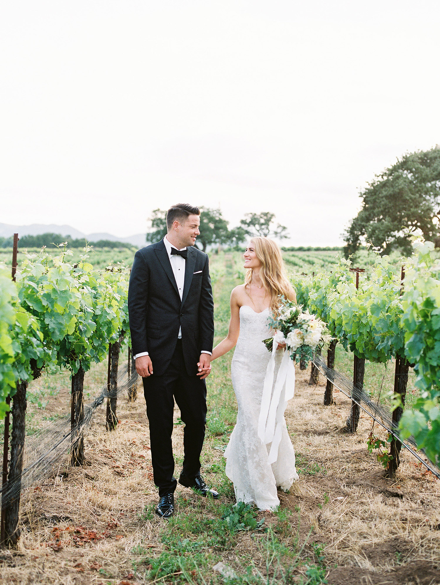 kati erik wedding couple holding hands in vineyard