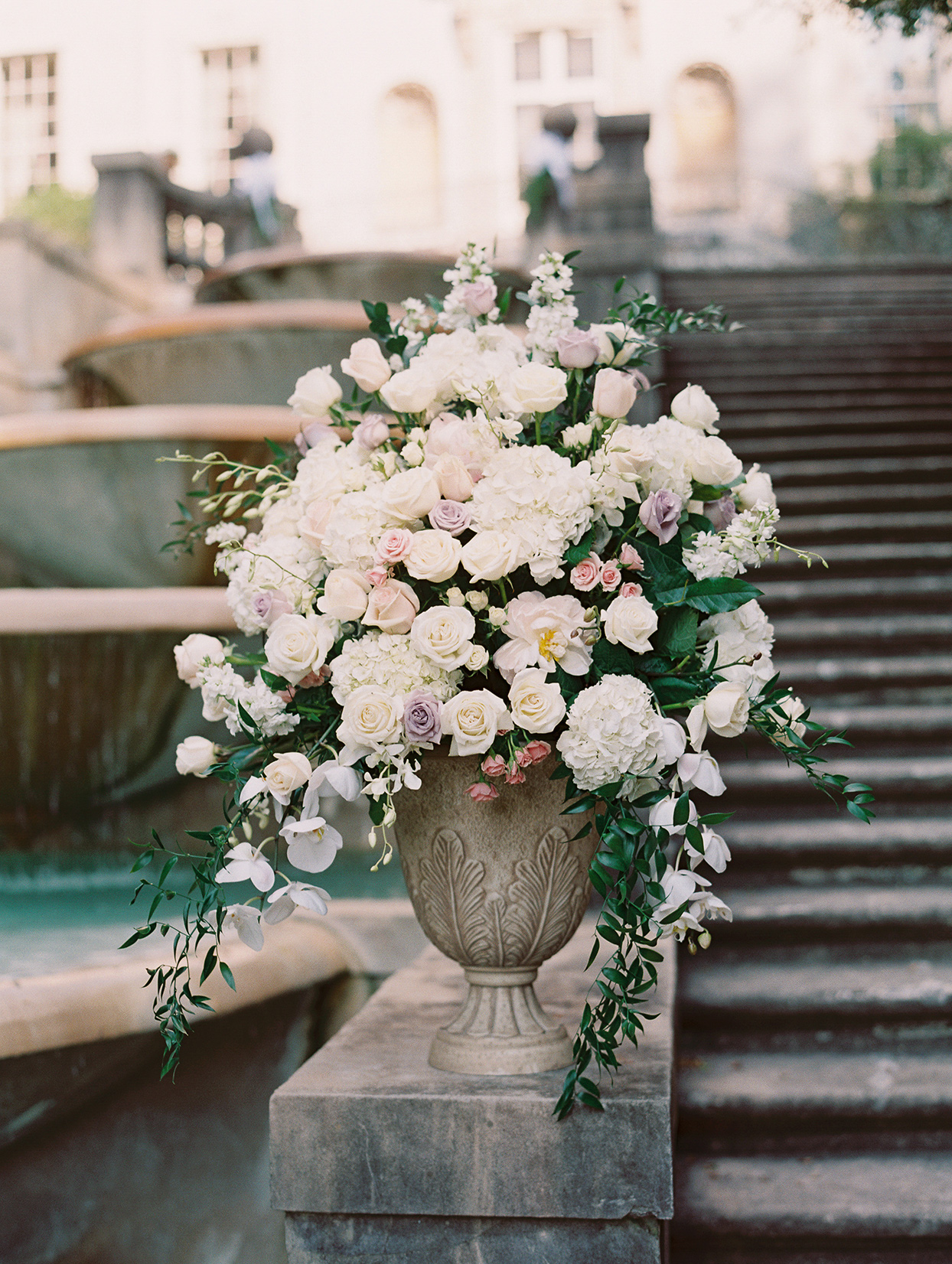 amelia justin wedding ceremony vase of flowers on stone steps