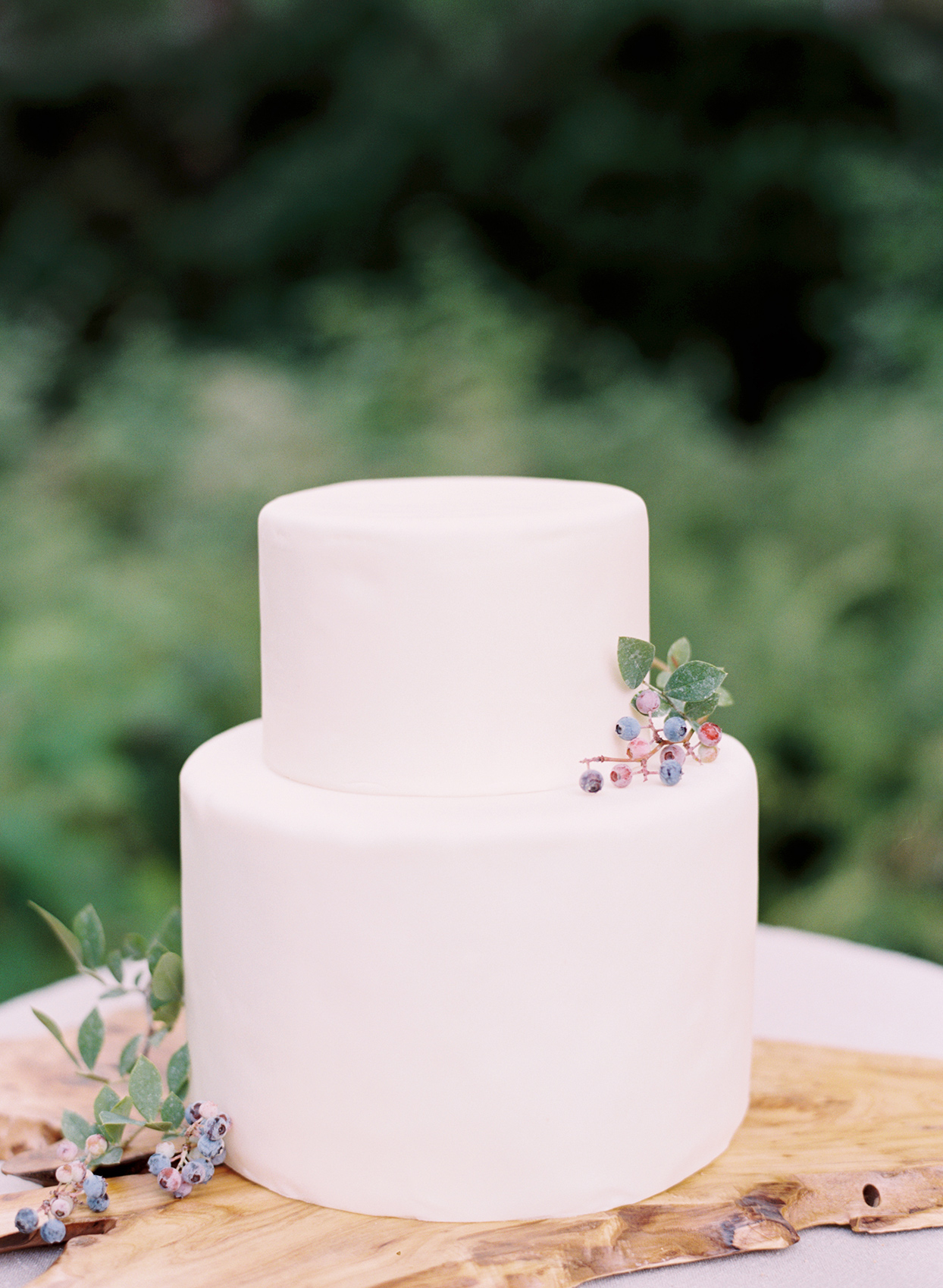 simple white wedding cake with berry sprig