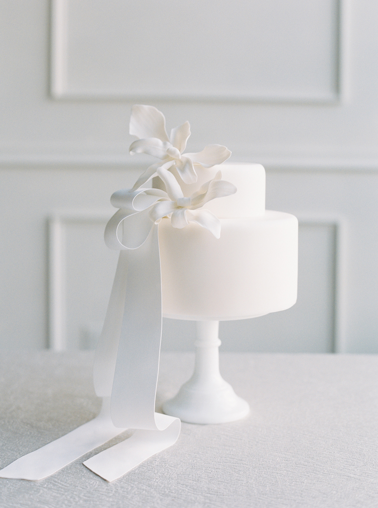 white wedding cake with abstract flower bow and ribbon