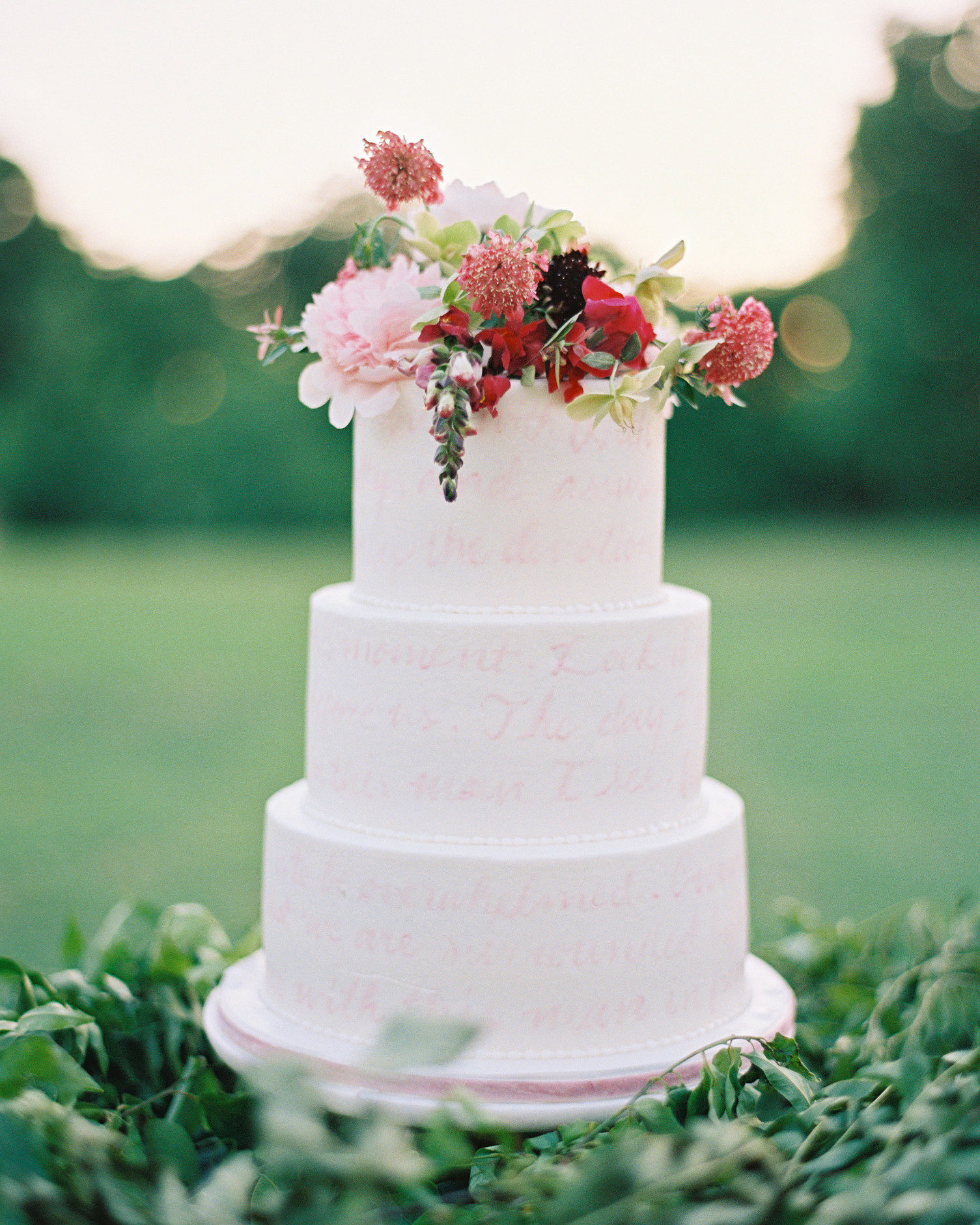 white wedding cake with pink vows and floral topper