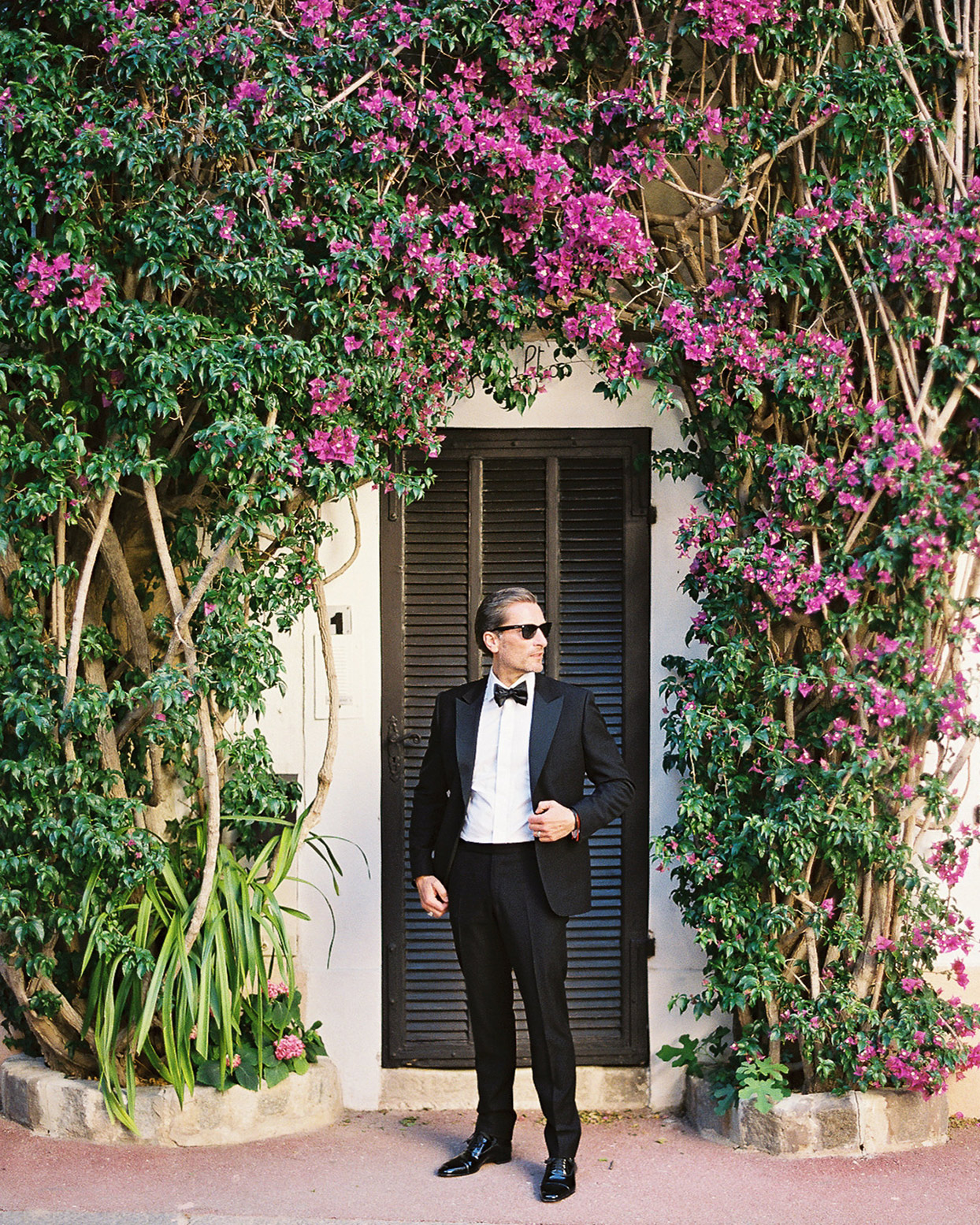 patricia ralph wedding groom in black in front of door