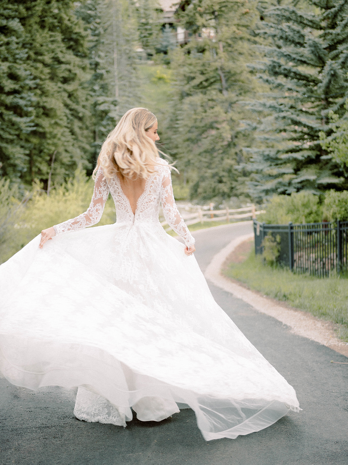 bride walking down wooded path wedding dress