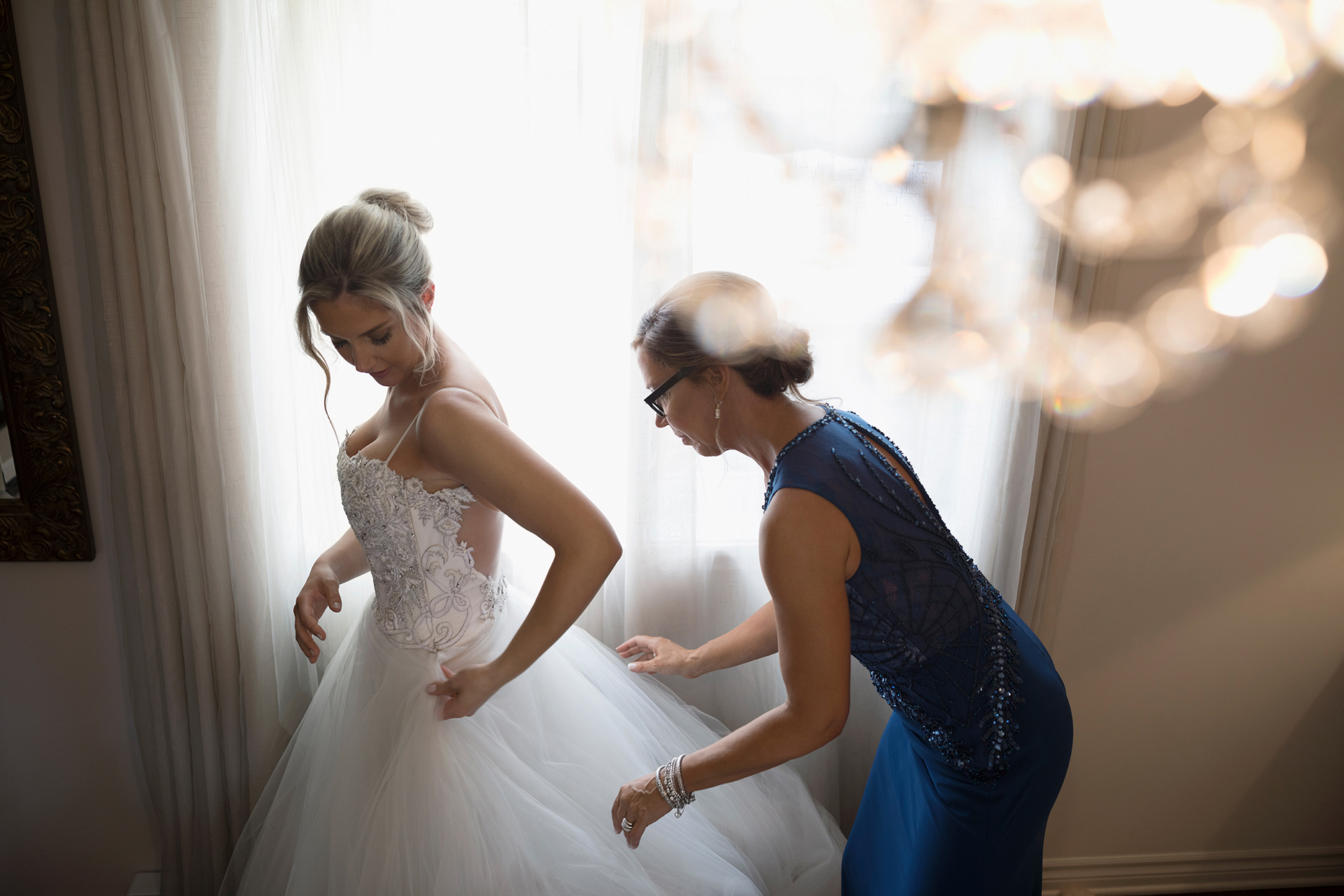 bride getting dressed with help of her mother on wedding day