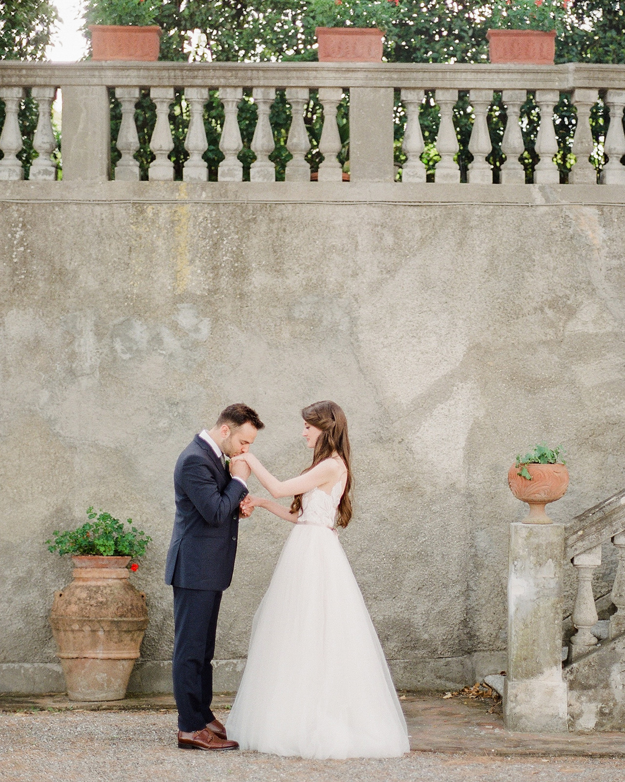 wedding groom kissing brides hand stonewall