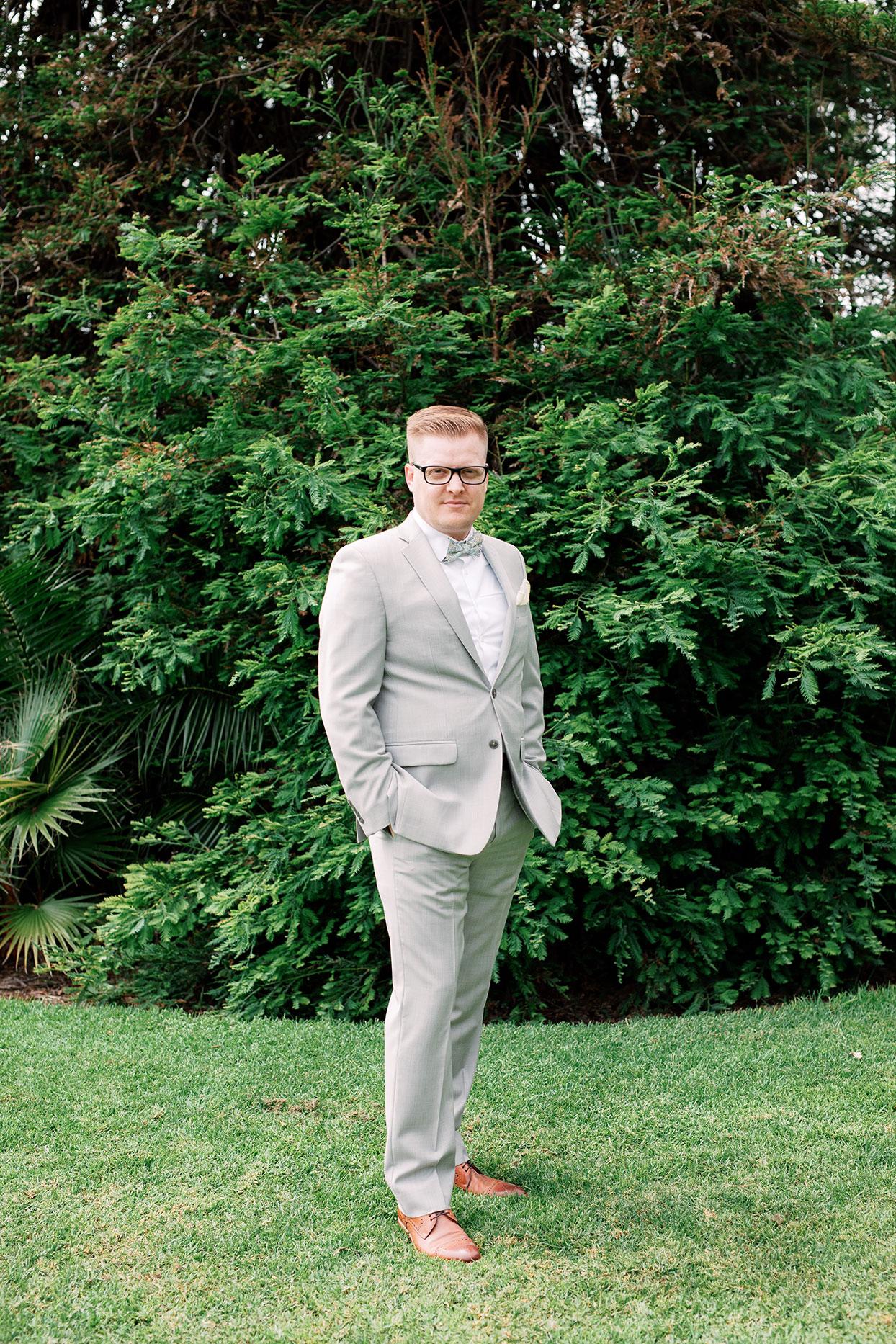 nina devon wedding groom in front of lush greenery