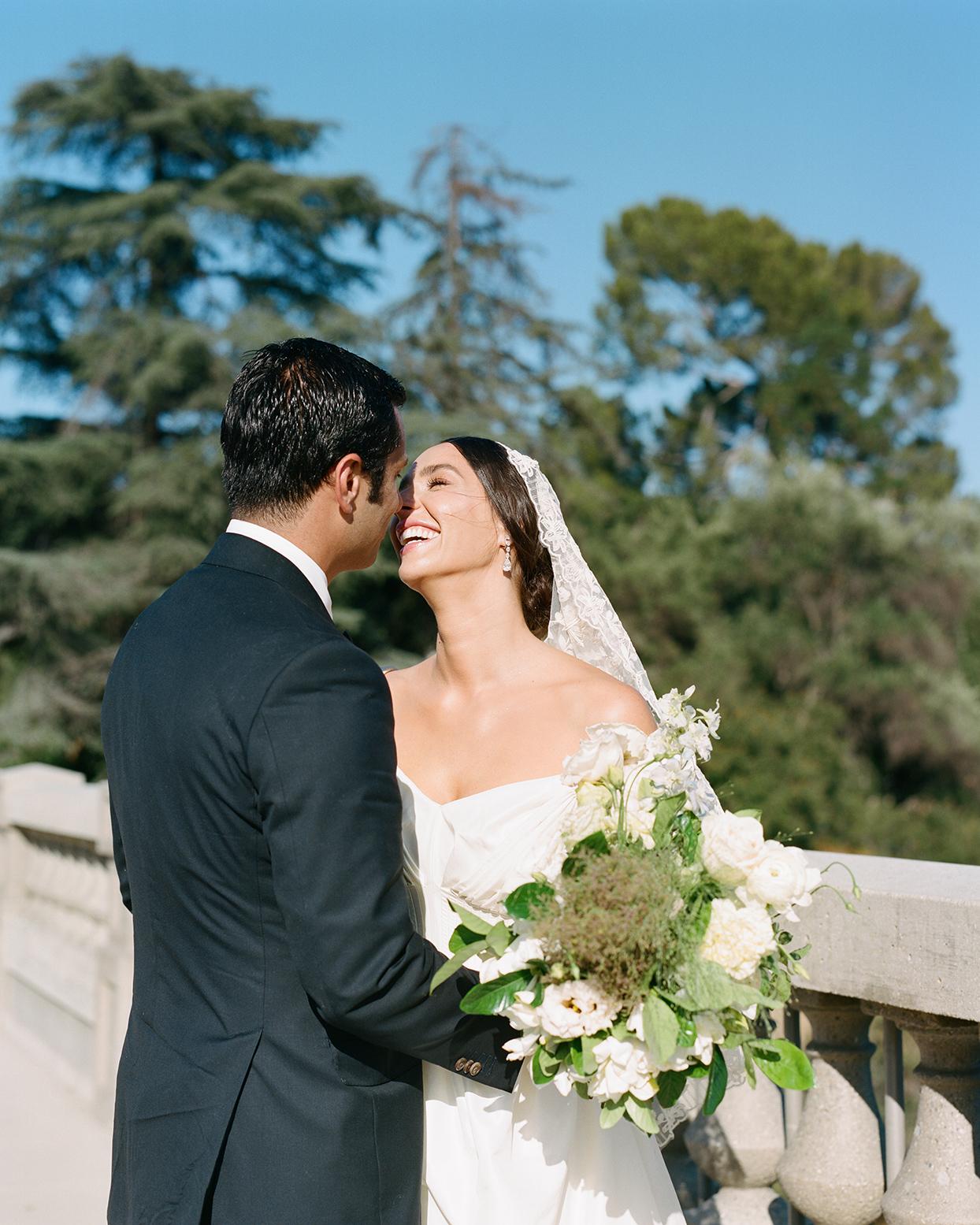 pia davide wedding couple against stone railing