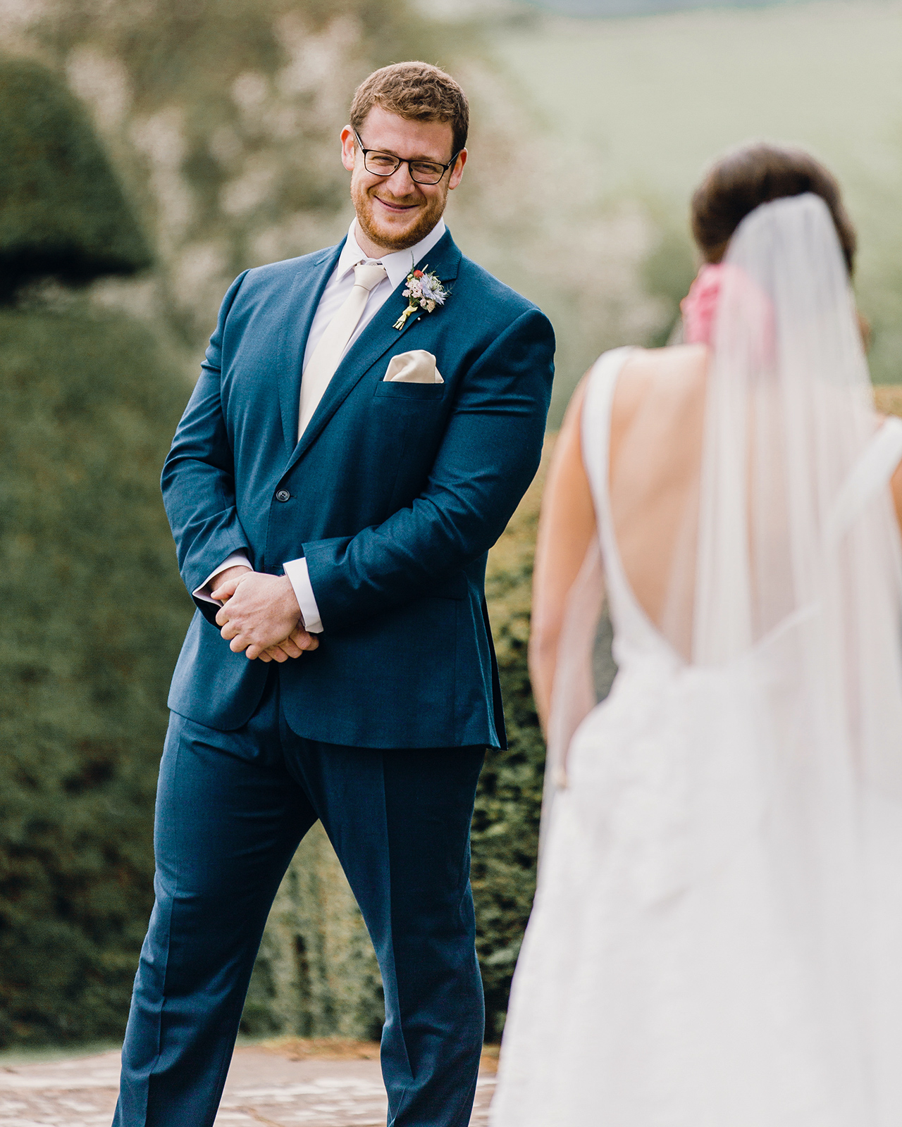 navy blue suit groom gets first look at bride