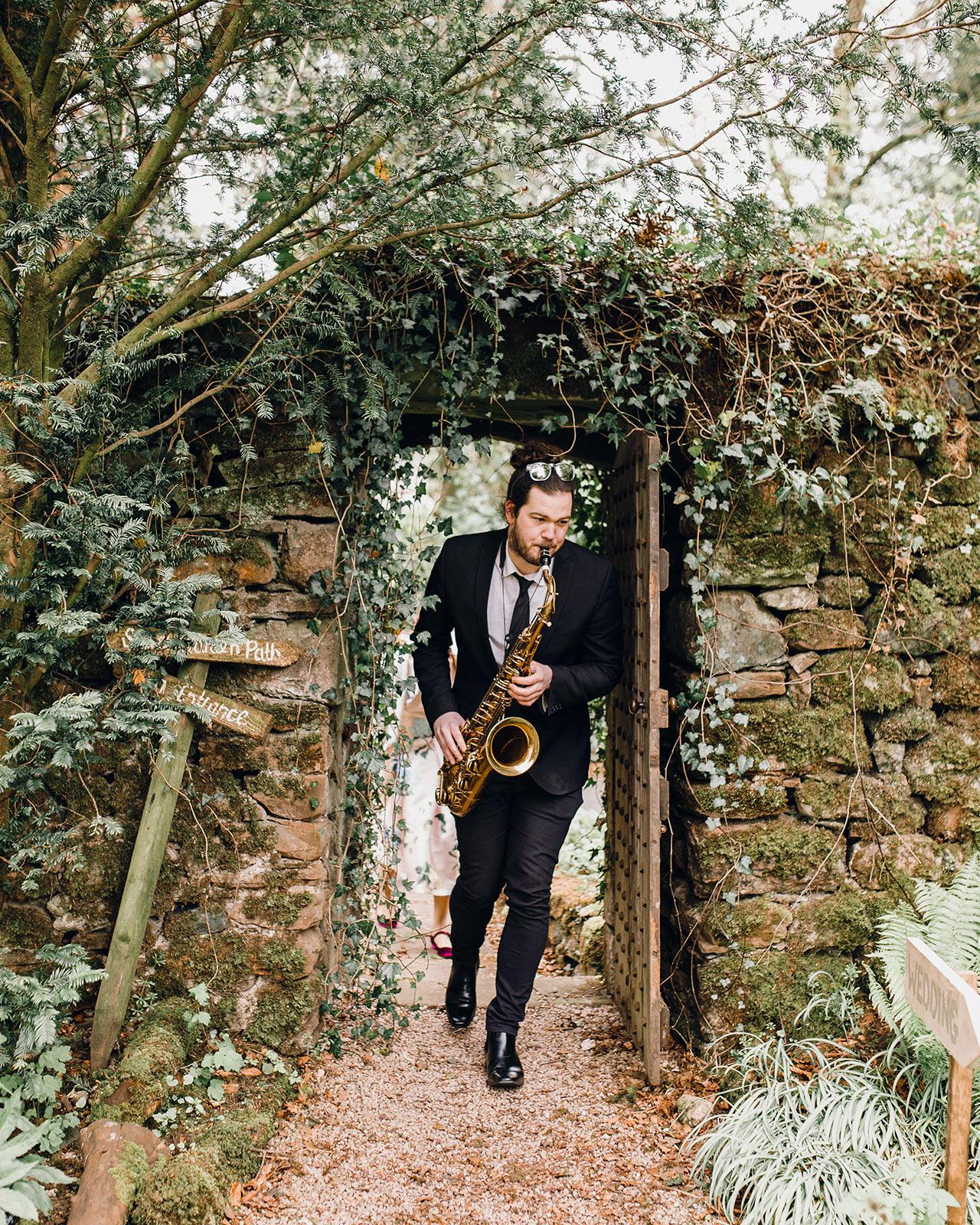 wedding saxophone player garden entrance