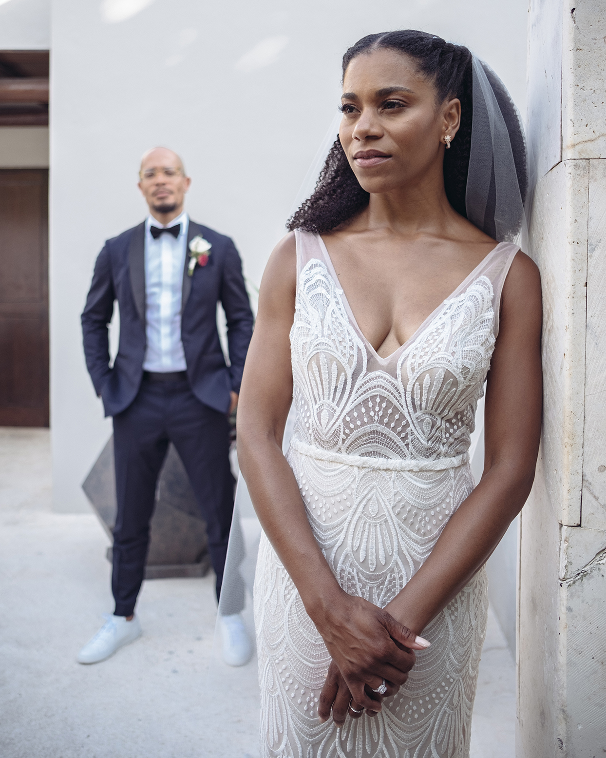 kelly mccreary standing in wedding dress in front of groom