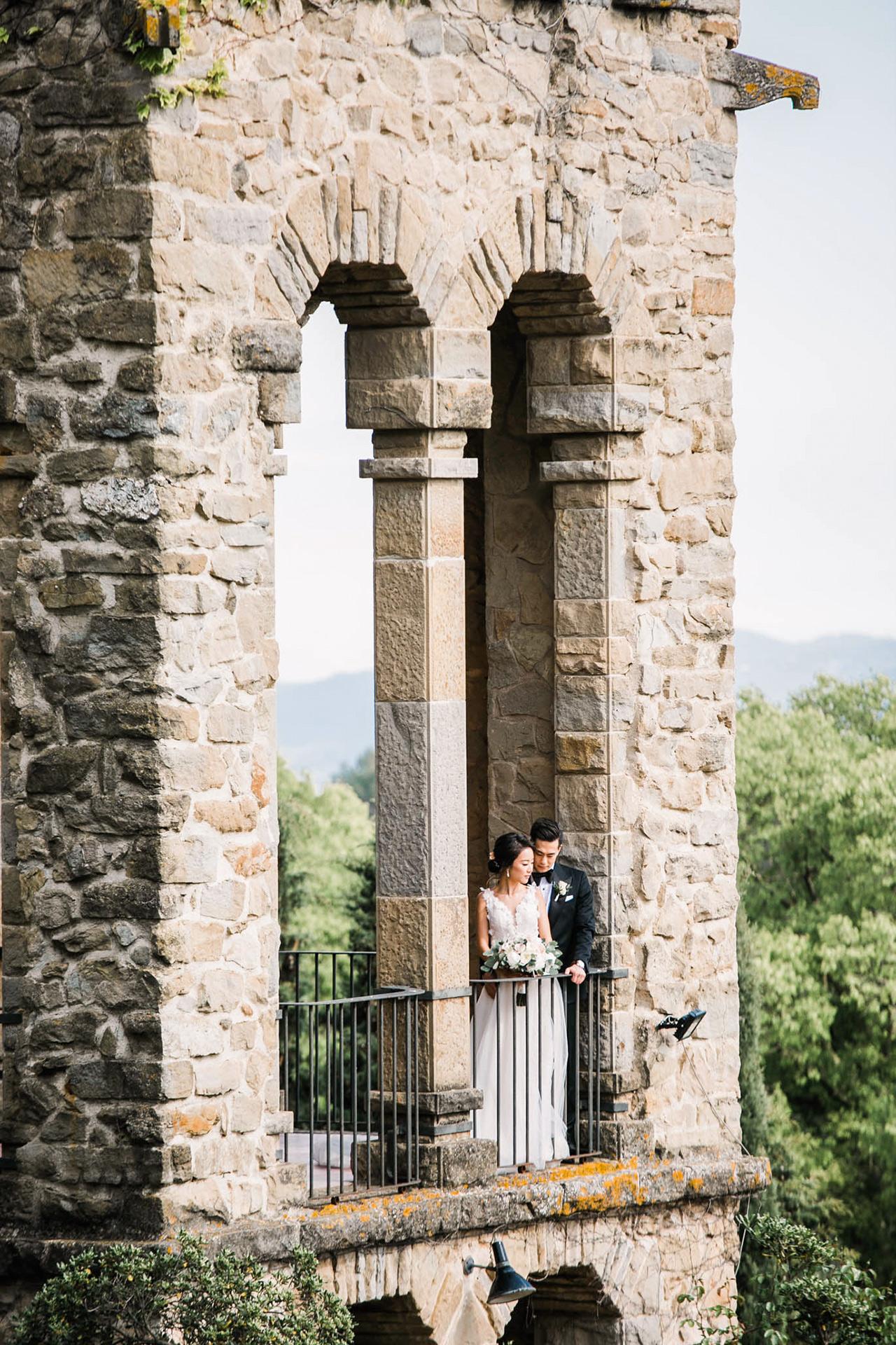 bride groom looking over stone building balcony