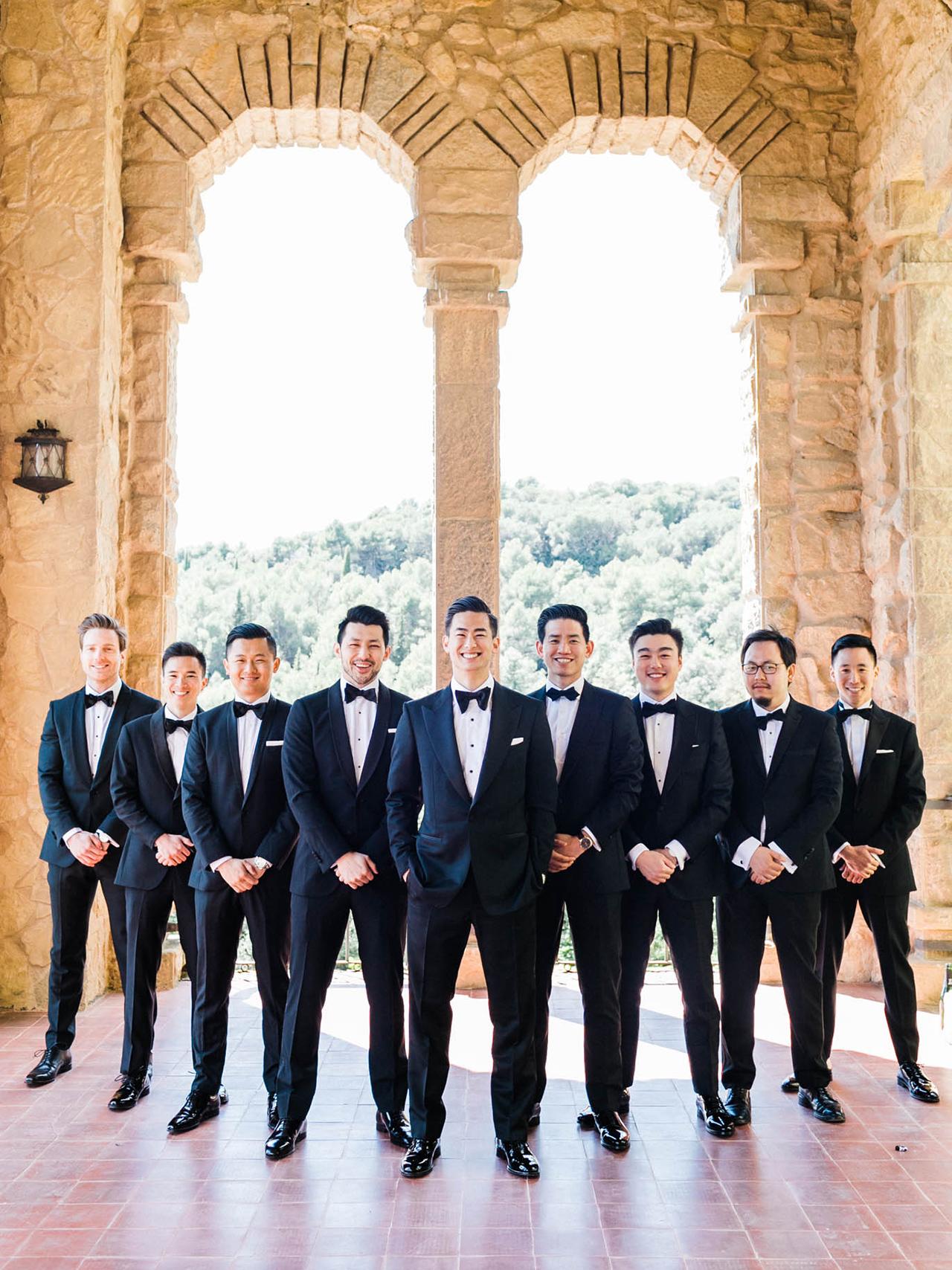 groom groomsmen pose in black tuxedo line up