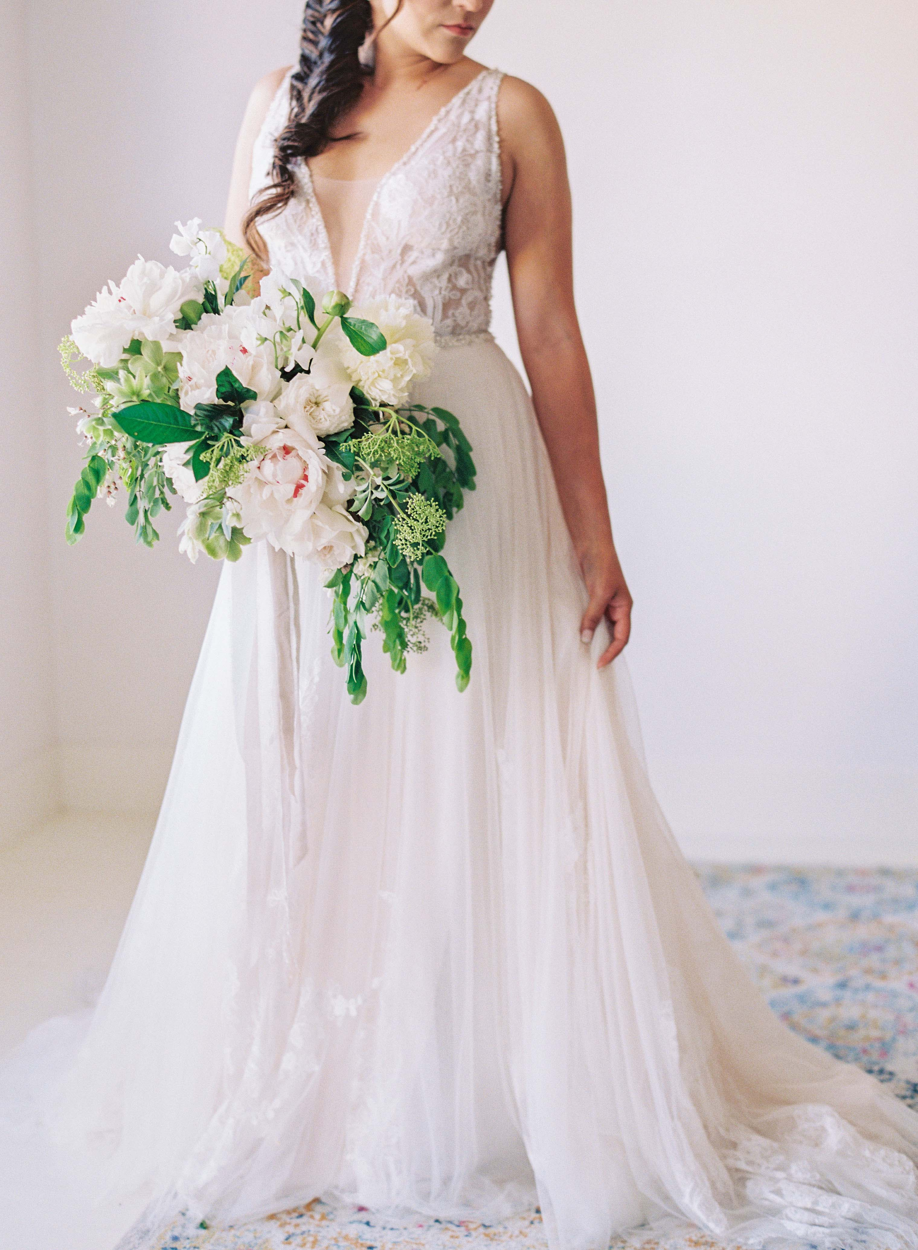 bride holding wedding bouquet of white flowers and greenery