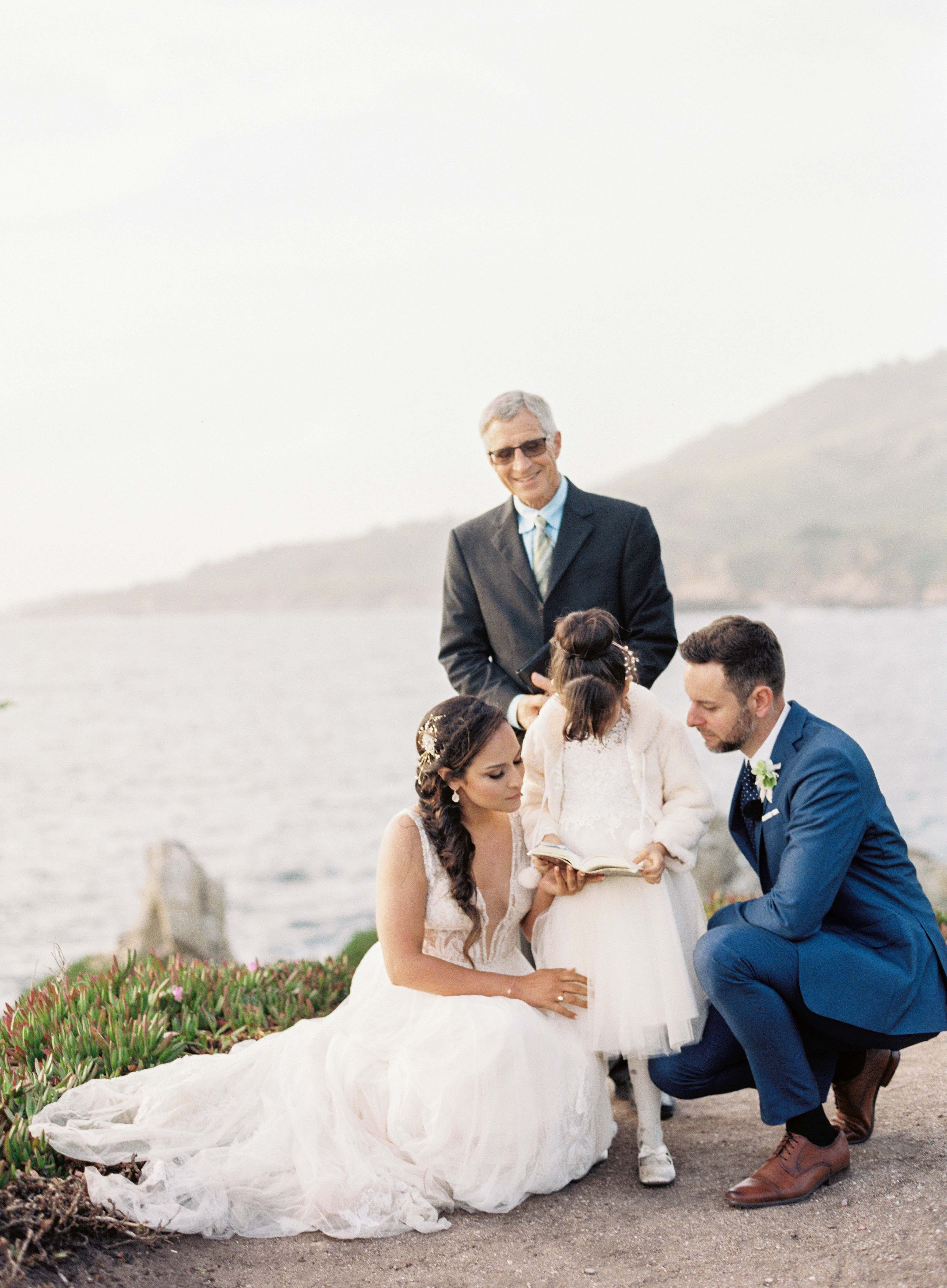 bride and groom kneel by girl outside wedding ceremony