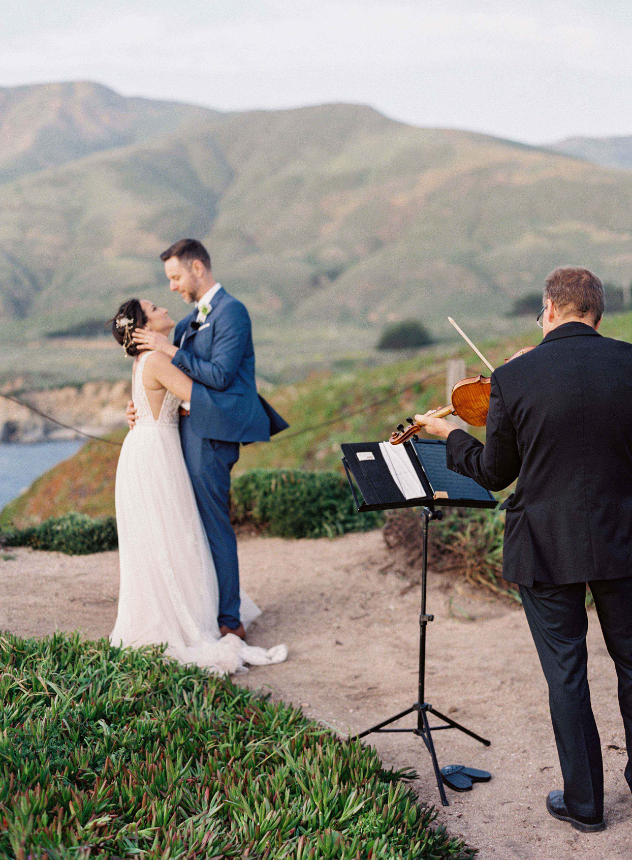 bride and groom dance outside on cliff