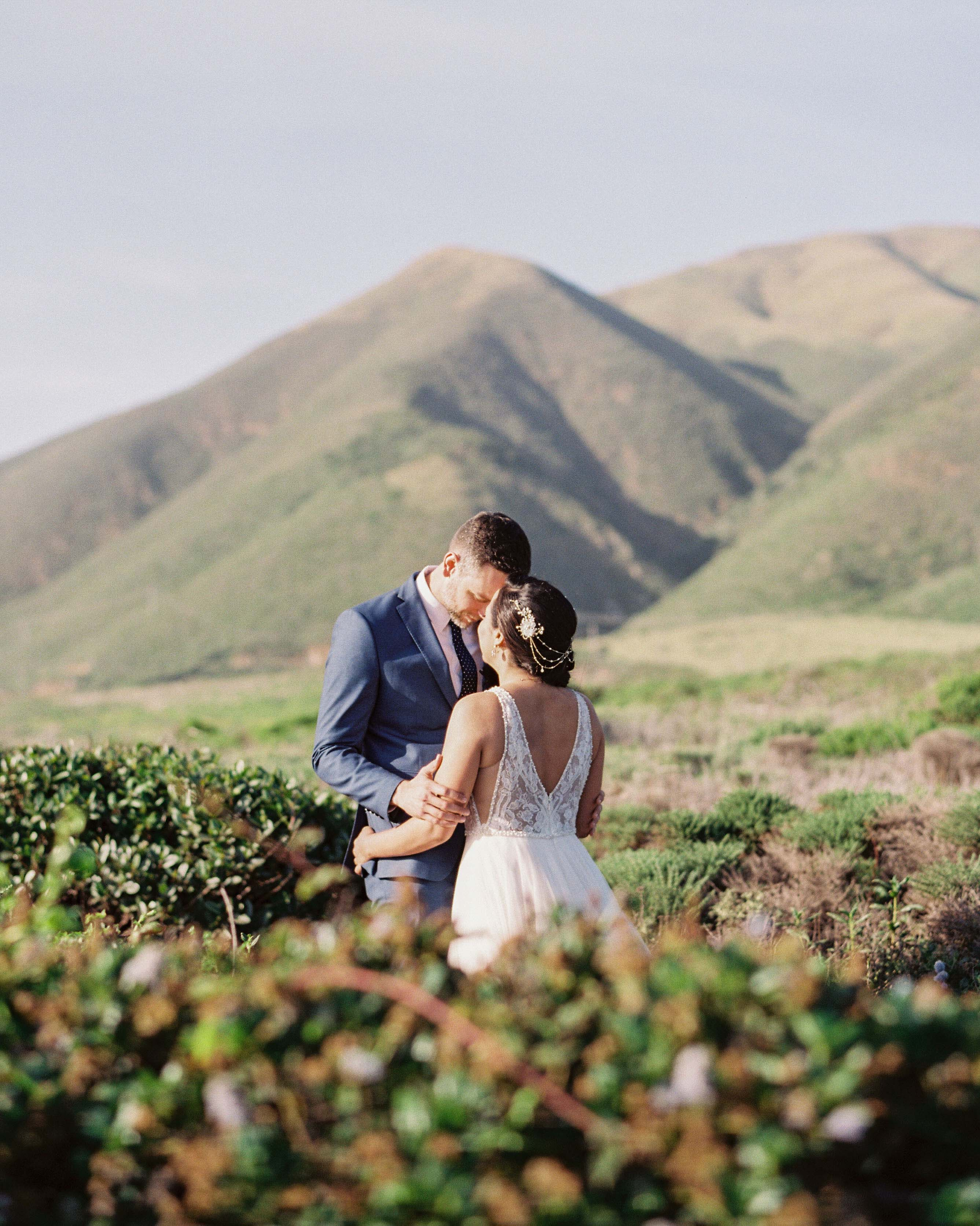 bride and groom stand surrounded by greenery outside
